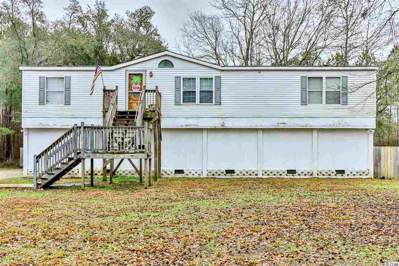 This 4 bedroom, 2 bath family home sits elevated just a stones throw from the Waccamaw river on a LARGE ONE ACRE lot. The updated kitchen features a breakfast bar and spacious dining plus a comfortable living area ready to become the gathering place for you and your family.  The large master bedroom features a large walk in closet and bathroom complete with a built in vanity unit! The spacious back deck provides the perfect place to relax and watch your kids playing in the HUGE fenced in backyard. Location and lot size will prove popular, so book your viewing today!