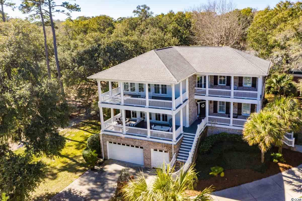 """There are too many wonderful highlights in this home to mention them all, but the first thing that comes to mind is it's beautifully serene setting with amazing outdoor areas and covered porches.  The all brick raised house exudes """"Southern Charm"""".  Located on one of the most beautiful golf holes of the Jack Nicklaus golf course in Pawleys Plantation, with added bonuses of marsh views and ocean breezes just out the door, location is premium. Some special interior features include:  all oak flooring throughout, big open spaces, gas logs in den and master bedroom, large eat in kitchen with island bar, granite and stainless appliances, a dream master suite with sitting area, a bathroom with stunning tub, his and hers vanities and walk in closets, unbelievable storage, additional heated/cooled unfinished bonus or recreation space on ground level, workshop, storage, laundry area off master bath, and 2 car garage plus a golf bay.  Tucked inside a very desirable gated golf community surrounded by rivers, wide beaches and in a central location to Charleston, Myrtle Beach, and historic Georgetown, many exciting adventures await the future residents.  Come see what makes this home so unique and desirable. Please verify all measurements and HOA information which is subject to change."""