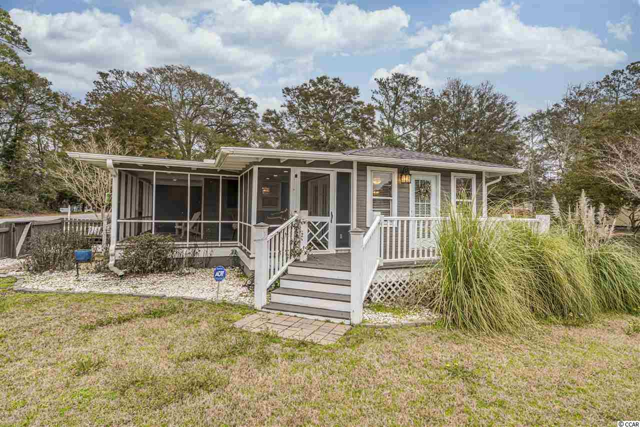 """Classic beach house charm meets modern appeal at this tastefully decorated home on a large, corner lot just steps to the Little River waterfront! Originally built in 1960, this home has been gradually updated from the inside out! While the previous owners updated all of the electrical and plumbing, the current owner has taken it even further painting the entire exterior and interior with neutral colors, adding a brand new HVAC, updating the light fixtures and fencing in the front yard! Imagine yourself taking in the salt air on one of two large porches: one completely screened in and one open air. Walk in off the porch eithera trellis covered, wooden deck and French doors into the spacious Carolina room with gorgeous travertine-style 18"""" tile, OR into your open concept kitchen! This kitchen is truly one of a kind with 16"""" ceramic tile flooring, stainless steel appliances, granite tile countertops, new tile backsplash and tons of cabinetry! The breakfast bar, complete with pendant lighting, flows seamlesslyinto the great room that features gleaming hardwood floors and recessed lighting. The two bedrooms are separated by an updated bathroom, complete with marble tile flooring, a shower/tub combo with marble tile to the ceiling, plantation shutters, and a vanity surrounded by white bead-board walls. Both of the bedrooms have ceiling fans, and the master bedroom has its own ensuite, also with plantation shutters, 16"""" ceramic tile flooring, a walk-in shower, vanity and full-sized washer/dryer. To top it all off, this property has no HOA dues AND the owner would consider selling ALL of the furniture!"""
