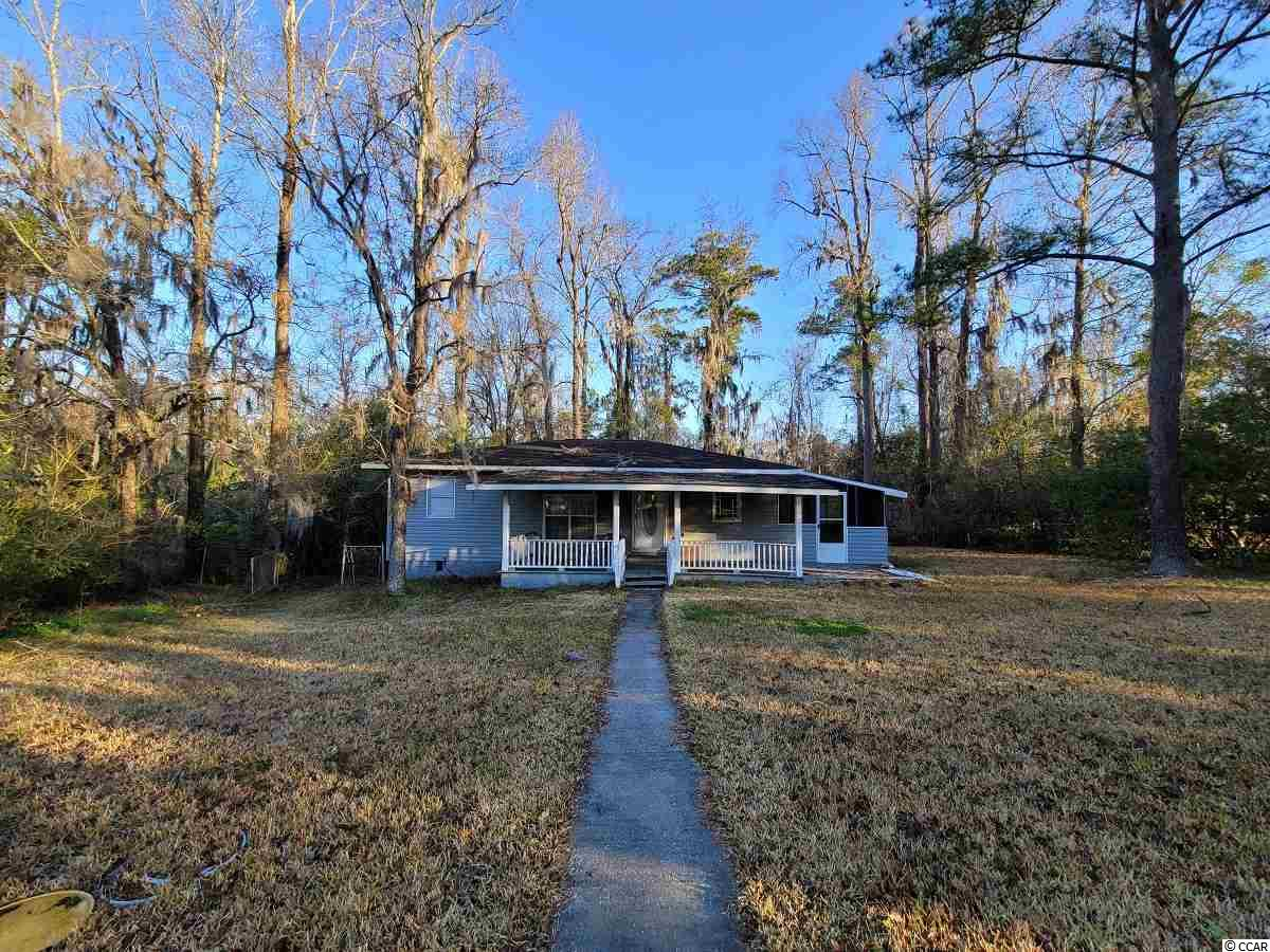 This home has excellent potential for someone who is willing to put a bit of work in. The home has about .7 acres just a 5-minute drive to Historic Downtown Conway, with a large fenced portion. Easy access to Myrtle Beach and North Myrtle Beach from Highway 90 or Highway 501.   Providing 3 bedrooms and 1 bathroom with hardwood floors through much of the home. A large living room leads to the bedrooms to one side of the home, and the dining room on the opposite. As you walk through the dining room the galley kitchen leads to a laundry/utility room. The is a detached building for storage and it's large enough for a workshop. Lots of space to enjoy the fresh air with a large front porch, screen porch, and rear deck. This house could be a great place to build sweat equity! Square footage is approximate and not guaranteed. Buyers responsible for verification.