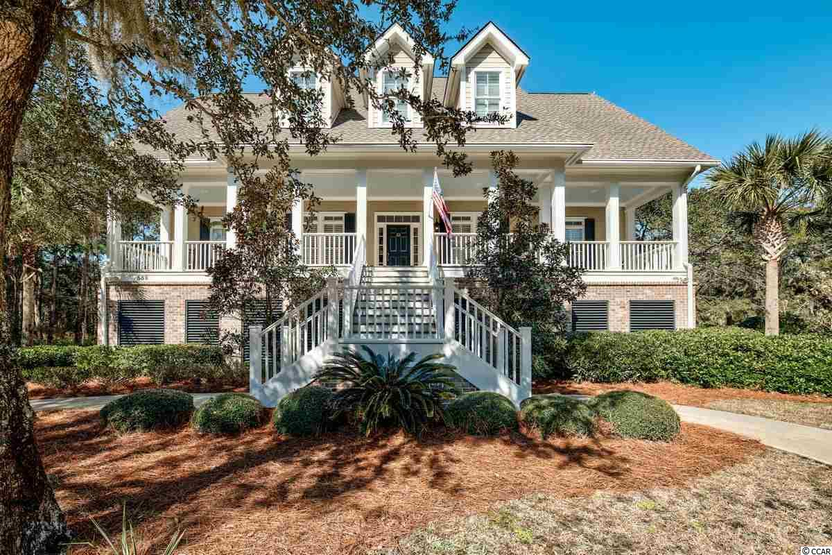 DeBordieu Colony - Pond Front - Low Country in the heart of DeBordieu. Wonderful layout and solid construction. Raised beach/low country style with Large lot, front porch, live oaks and attractive landscaping set the stage for this attractive home. The 2nd floor main level has gorgeous heart pine floors, and open kitchen, dining, family room layout with fireplace, laundry room, the master suite and a private office. A huge screened porch in the rear stretches the length of the back of the home overlooking a large fenced yard with oaks and pond in the distance. The third floor is for your guests - 4 Bedrooms 3.5 Bathrooms and a cozy den. Elevator access to each level and lots of storage space. The ground level has a huge outdoor shower with hot/cold water, a half bath and a storage room. The three car garage provides plenty of room for the carts, boats toys etc. other features include tank-less hot water heater, gas range, and more. This is a must see and wont last long. DeBordieu Colony is an oceanfront community located just south of Pawleys Island, South Carolina featuring private golf and tennis, saltwater creek access to the ocean, a 24 hour manned security gate, and luxury homes and villas surrounded by thousands of acres of wildlife and nature preserves. People who have been here say there is no place like DeBordieu. Come see for yourself!