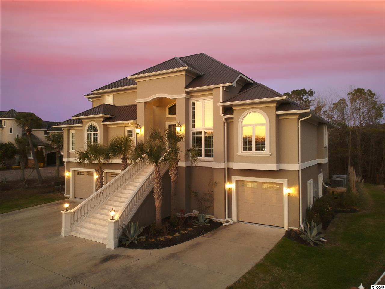 This elegant custom-built, 4-year-old home boasts three beautifully maintained levels, accessible by dramatic staircase or private elevator.  The residence sits at the edge of a marsh along the Intracoastal Waterway on the west side of Cherry Grove.  A drone view demonstrates this ideal location in an upscale neighborhood without HOA.  This one-of-a-kind gem, perfectly highlights the unique designer touches throughout.  First time to market with only one owner.  The main floor contains a dramatic two-story living area, complete with modern ventless fireplace and unique one-story lighting fixture.  Beautiful furnishings are included with this property, such as custom sofas and tables, electronics and custom window treatments (remote-control sheers in living area).  The open design incorporates a stunning dining area and fully accessible kitchen.  The envy of every chef...stainless steel appliances compliment quartz countertops and 6-burner, with integral griddle stove.  Each night relax to the jewel of the house...the master suite.  The master encompasses the entire third floor with stunning views of the Intracoastal from the two-person, jetted bathtub.  His and her sinks as well as walk-in shower allow space for both, along with an incredibly large closet with built-ins to satisfy any designer diva.  Fall asleep in the custom-made king-size platform bed while watching the fire dance in the see-through fireplace.  Storage is abundant with parking for 5 vehicles in dual garages.  Additionally, boats and other toys can be stored to the side, as no HOA exists to restrict.     Four full bedrooms with 3.5 baths incorporate enough room for family time and comfortable entertaining of friends.  A California bathroom connects two of the three spacious bedrooms on the main floor and roomy walk-in closets were designed for great storage.  The base level has been finished for an additional 925 usable, heated square feet which can be utilized as a separate playroom, in-home theater or private office.  The backyard is expansive enough to add a pool.   Three decks along the back of the house provide for outside entertaining with marsh views, complete with full furnishings and CAT 5/6 power hook-ups hook-ups for your favorite electronics on the ground floor.