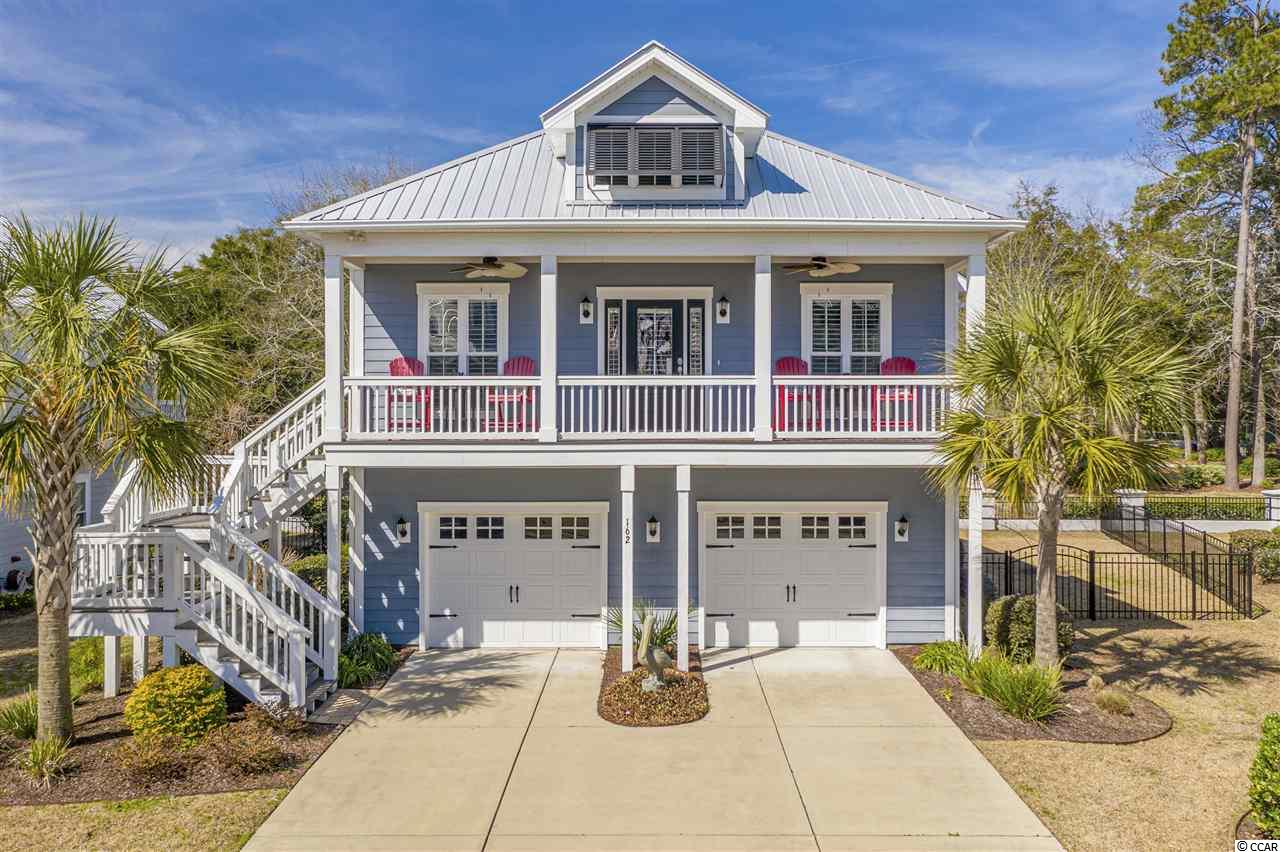 This is a beautiful raised beach home located in the secluded and prestigious South Bay Village. South Bay Village is a gas community located just minutes by golf cart from the Murrells Inlet Marsh Walk for great dining and entertainment. This home has an oversized 2-car garage and finished ground floor flex room for an office or extra bedroom. Sit on the front porch or the back and enjoy the nice sea breeze from the marsh. Beautifully landscaped with a fenced in backyard. Inside is a luxurious open floor plan with hand scraped hard wood floors, 10' high trayed ceilings, and gas fireplace in the living room. If you love to cook, you will love this kitchen with a huge work island, granite counter tops, stainless steel appliances, and gas stove top. The master bathroom is your oasis. Multi head tiled shower and a stunning claw foot tub provide you with luxury and elegance.  This home is ready to be seen and it won't last long! Schedule a showing today!