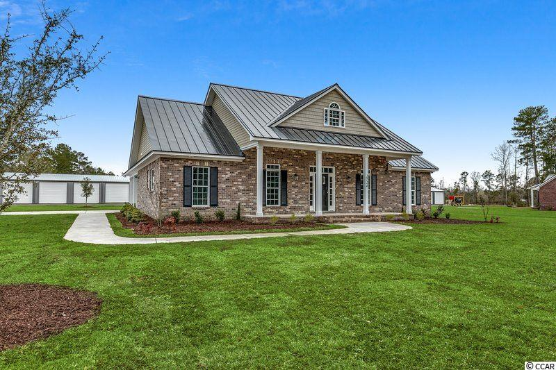 Custom all-brick new construction on 1.3 acres with a detached metal building that is over 4000 square feet! No HOA. Statuesquely positioned in a country setting, this home invites visitors with warmth, southern charm, and a deliberate, yet subtle sense of something truly special. Crossing over the low-country-style front porch and through the front door, the spacious living room greets you. This area is highlighted by luxury vinyl plank flooring, built-in shelves and cabinets, shiplap, and a fireplace with gas logs. Moving through the living room, you'll find the gourmet kitchen. You'll love the convenient central location as well as the custom cabinetry, soft close drawers and doors, gas stove, granite countertops, and a work island. The open flow of the kitchen allows for an abundance of space for the dining area. Split and functional floor plan. Two large bedrooms feature oversized windows and each have a spacious closet with built-in shelving. The master suite features a ceiling fan, trey ceiling, and an ensuite bathroom. The master bathroom contains dual sinks, a garden tub, a separate tiled shower, and a walk-in closet with generous space for storage. Back in the hallway, the laundry room has a lot of cabinetry for storage and a sink. Enjoy your coffee on the covered porch that has a fan, gas hookup, and overlooks the back of the property. The attached carport has a closet for additional storage. Following the paved path from the carport will lead to the detached building with seven 12x12 garage doors. This massive building features plenty of garage area for parking recreational vehicles, boats, tractors, and more. The far end of the building features 900 sq. ft. of heated area with a bathroom. A perfect area to be finished for a guest space, an office, or a workshop. The building has a 200 amp service, internet cable, and gas hookup. There are many thoughtful details and upgrades to appreciate here including the 26 gauge standing seam roof on the house and t