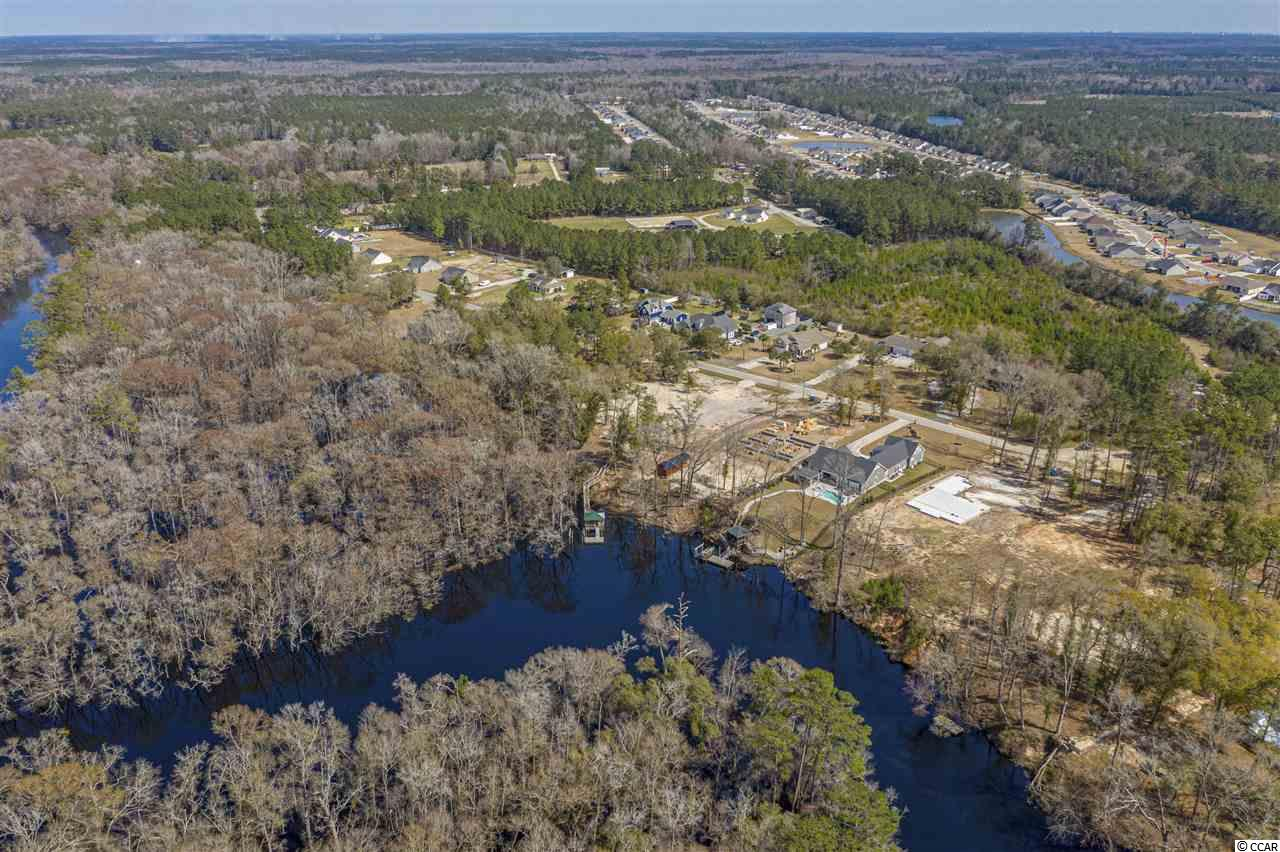 Come live the life that you've always wanted on the Waccamaw River! This huge 2.16 acre lot is located in the peaceful community of Bear Bluff Plantation! Come enjoy the freedom of having NO HOA! Why fight for a house that someone else has lived in, when you can build your brand new custom home on this one-of-a-kind lot! Turns out....you can have it all! This is a fisherman's dream! The dock and 10,000 lb. boat lift were both recently added. This river connects directly to the Intracoastal Waterway, which you can use to travel up to several islands just north of Cherry Grove or you can take it down to Winyah Bay! Either way, the ocean is easily accessible. Therefore, you can enjoy freshwater or saltwater fishing any time your heart desires! This property sits high on a bluff and the buildable portion of the lot is in zone x, so you could build a single-level ranch if you wanted to. The tap fees have already been paid to Grand Strand Water and Sewer, and the meter has been installed. Public sewer is available. This lot has been cleared, and it's ready to build on! Some trees remain in the backyard. This would be the perfect place to relax in the shade or do some stargazing on a nice southern summer night! This is an extra-large lot, so there's plenty of space for privacy. Two lots were combined into one. There are several upscale homes in the neighborhood, and Shaftsbury Glen Golf Course is only a few minutes away. Motorcycles, golf carts, RVs, four-wheelers, and dirt bikes are all allowed! Why get rid of all your toys, when you could build a garage big enough for all of them! The best part about this area is that you feel like you're in the country, but you're still close to everything that the Grand Strand has to offer! International Dr and Hwy 22 are both very close by. This is a highly desirable area, and the beach is only about 20 minutes away along with several golf courses, restaurants, and places to shop. Barefoot Landing, Duplin Winery, and the Tanger Outlet