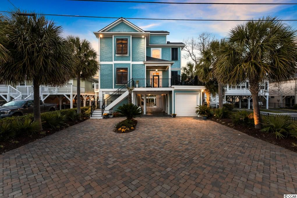 Come take a look at this stunning raised beach home located on the Channel at Cherry Grove Beach. This home has been recently remodeled with very luxurious finishes. Enjoy the convenience of the elevator from the ground floor to the front foyer, where you will find a beautiful rod iron staircase with wooden stairs leading to the second floor which can also be accessed by the elevator. On the first floor you will find a large open concept living/dining/kitchen area with exquisite finishing's. The kitchen has a tray ceiling, granite counter tops, can lights, stainless steel appliances, lovely tile backsplash, refrigerator, dishwasher, and stove and a storage closet off the kitchen. The lovely hardwood floors span throughout the entirety of the home. In the dining you can envision having large dinner parties with all your friends or family. Moving into the living room you will see the beautiful crown molding, gas fireplace, custom built-in shelving, two ceiling fans, and a beverage bar. The living room also expands out to the first floor screened in porch with multiple ceiling fans for your comfort. There is also a guest bedroom and full bath with vanity and tub/shower combo with tile on the first floor, just off the main living area by the kitchen. This bedroom also has a large closet and ceiling fan.  Heading up the rod iron and wood stairs you will come to the upstairs foyer and hall area. There is a stackable washer/dryer laundry closet, a 2nd and 3rd guest bedroom, and another full guest bath with tub/shower combination with tile walls, a single sink, and tile floors. The 3rd guest room also has access to a large screened in porch and additional uncovered upper deck area with captivating views of the channels, inlet & marsh.  The upper floor also has a lovely master suite with double doors to a screened in porch. Attached to the master suite, you will be awestruck by the astonishing master bath with tile floors, a glass tile shower with rainfall shower head, built in tub with tile surrounding, double sinks, and 2 closets. This home has an incredible well landscaped yard with a lovely swing to sit out and enjoy the views from the ground floor. There is also an outdoor shower at the back of the house on ground level for your convenience.   Some other special features of this home are its golf cart garage, Trex porches and decks and pergola area, tile driveway underneath the home, driveway entrance is completed with pavers. There is a floating dock right on the channel. A large climate controlled split storage area on ground floor level, Hurricane shutters on the entire house, music in every room & outside speakers on the second and third floors. Surround sound in family room & master bedroom. Security system. Plantation shutters on all windows throughout home. LED night lighting and sprinkler system. All drapes and window treatments will remain with home, as well as most of the furniture. Don't miss out on this opportunity to enjoy beach life at its finest. You are conveniently located just a golf cart ride to the beach, and a short drive to all the shopping and dining of North Myrtle Beach.