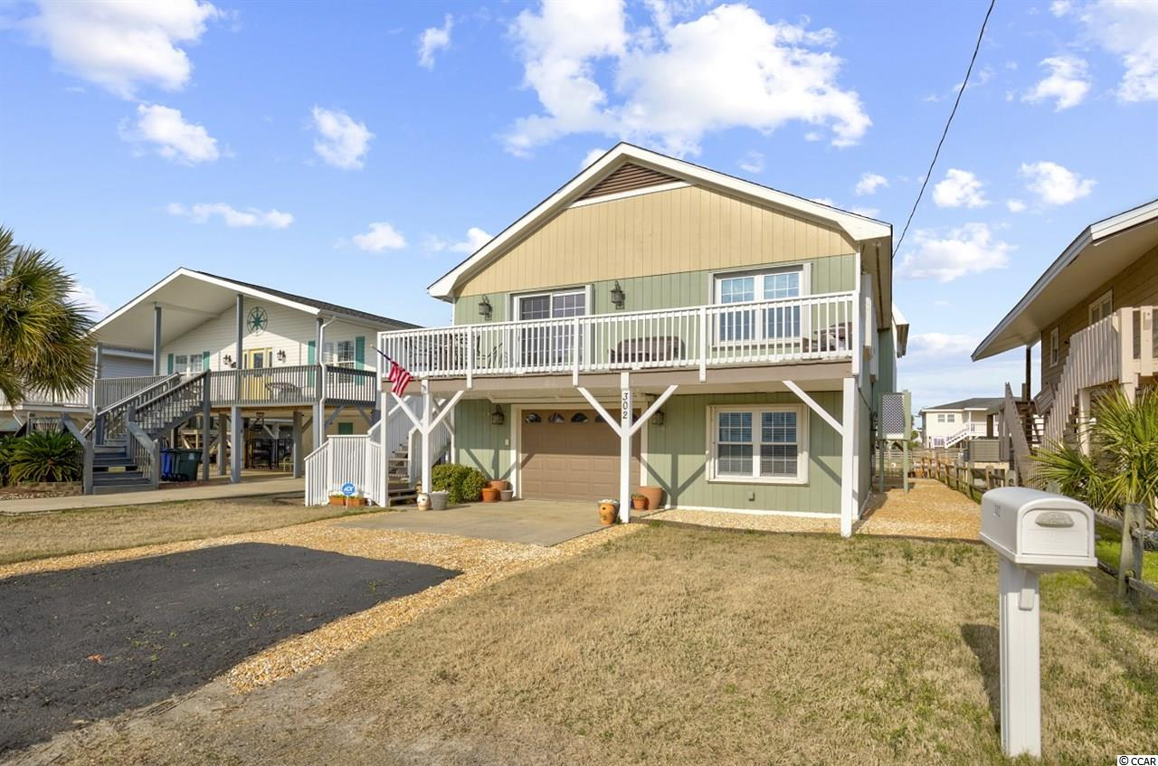 """This classic channel home boasts five bedrooms and is located on a highly sought after street in Cherry Grove, just a few short steps to the beach - no golf cart needed!  This is a rare opportunity  to own a channel house this close to the ocean, and for those who enjoy fishing, there is a public boat landing and fishing  pier just three blocks away - or if you prefer, enjoy boating, fishing, kayaking and swimming in your own back yard.  There is a floating dock for your enjoyment and canoe/kayak storage beneath the house.  This house has been lovingly maintained and tasteful updates added to enhance the home's original charm - and charming it is!  Wake up to wonderful water views in the spacious master bedroom, which also features a large walk-in closet.  The kitchen features granite and stainless steel appliances, and the home showcases high ceilings with exposed beams, as well as an interior oversized laundry room and interior stairs to access both levels.  You will enjoy the ocean breeze from one of three outdoor living spaces, including a large upper back deck overlooking the  channel,  spacious living space beneath the home also facing the water, and a front deck, from which you have a view of the ocean and the marsh!  There is an outdoor shower for rinsing off the sand after a day of sun and fun on the beach.  The garage is perfect for your auto, golf cart, and/or storage.  There is additional exterior storage space, and storage galore inside the home with two large floored and insulated attics (one walk-around, so you won't bump your head!)  Commercial grade hurricane shutters are installed on every door and window and will convey with the home.  This house provides easy access to golfing, dining, entertainment, shopping, and all that North Myrtle Beach has to offer!  Although the owners used this home as their """"home away from home"""" and never put it on a rental program, this house with five bedrooms, would be an excellent rental property.  It also presents a"""