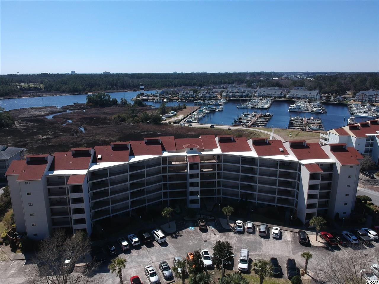 You have to see this rarely available upper floor 3 BR 3 BA condo, overlooking the marsh, intercostal waterway and beautiful Coquina Harbour.  The black and white Iconic Little River Lighthouse is in view as soon as you enter this well appointed condo, waiting for you to call it home.     The condo features wood flooring and coffered ceilings that grab your attention as you enter.  The wood flooring is in the entry and continues into the combination living and dining area.  The kitchen and baths have ceramic flooring with updated cabinetry and fixtures.  All three large bedrooms have carpeted flooring.   This 3 BR model is the split bedroom design, with the master suite on the opposite side of the living area separated by open space from the other two bedrooms.   The master suite features a large bathroom with a ceramic walk in shower and master bedroom with direct access to the large covered patio.  There is a guest bedroom, often referred to as the second master, with an on-suite bath as well.  The third bedroom has a full bath located just outside the bedroom door.  All the room makes for great visits with family and friends.  These buildings are known for their great outdoor living  space which in this model is even larger as it wraps around to the master suite.  The building is constructed of concrete and steel with stucco providing for the ability to utilize your gas grill on the large oversized deck, unlike most condominiums.  The balcony/porch has room for plenty of seating, making for unusual opportunities to enjoy the beautiful SC weather while viewing you prized boat in the harbour.  Should Dark Skies and winds arrive, the patio has built in storm shutters.  This home also boasts of a large indoor storage room directly off of the foyer as well as a large laundry directly off of the kitchen.  Little River is a small fishing village that has remained unincorporated and has a vibrant waterfront on the intracoastal and gambling casino boats to enjoy beyond th