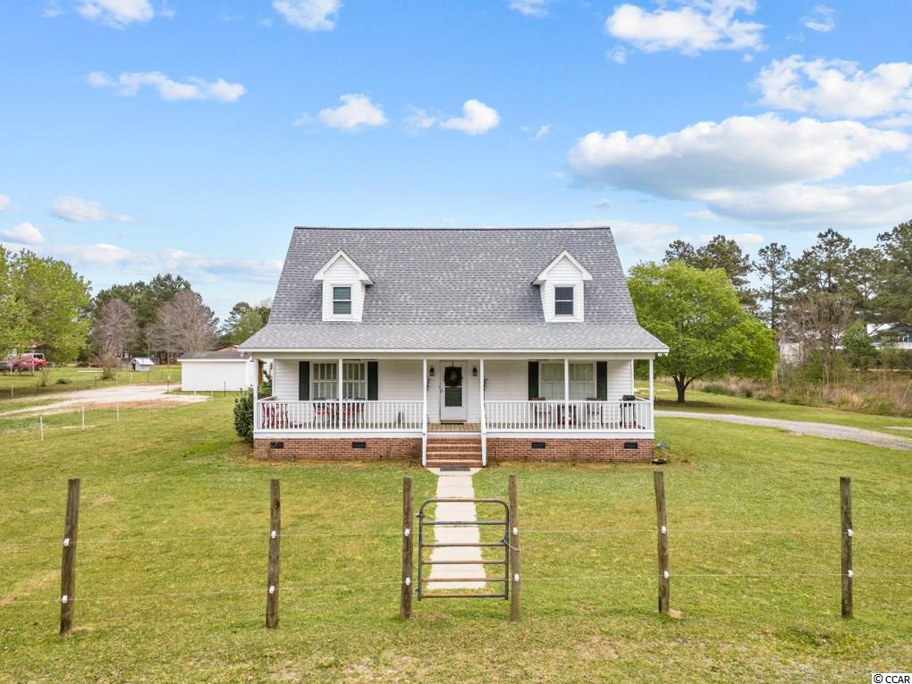 You have to see this true HORSEMAN'S COTTAGE, located in Conway, SC and convenient to all the area has to offer!  This adorable 2100 sf Cape Cod has such curb appeal!  See the 45 foot wide FRONT PORCH that welcomes you home as you come up the long drive.  This rocking chair front porch is one you could spend some time in! Once you step into the home, you're in a semi-open floor plan with a large living room that boasts a gas fireplace with built-ins.  Walk further through to the dining area and country kitchen that overlooks the 14x14 screened porch and equestrian property!  There is a dedicated laundry/mud room and spacious closets and lots of storage! The home features 3 bedrooms, with the owner's suite on main level, and 2.5 baths.  Upstairs is a large loft/landing big enough for a cute office, playroom, or any kind of flex space!  Stepping outside, there is a custom built 24x55 BARN with 4, 12x12 STALLS and a feed/tack room.  Could easily add on more if needed!  Current owners had 6 horses comfortably on property. There is a 100x130 RIDING ARENA area and a 12x16 outbuilding with a lean to on a concrete slab.  This hobby farm is located in a small COMMUNITY OF HORSE LOVERS that take community trail rides on the weekends, and look out for each other.  Property is zoned Farm Agricultural.  Farm is located 2 miles to endless dirt roads for great trail riding.  This home has great bones but needs a little love and updating.  Come enjoy your morning coffee on either of the porches while watching your horses graze.