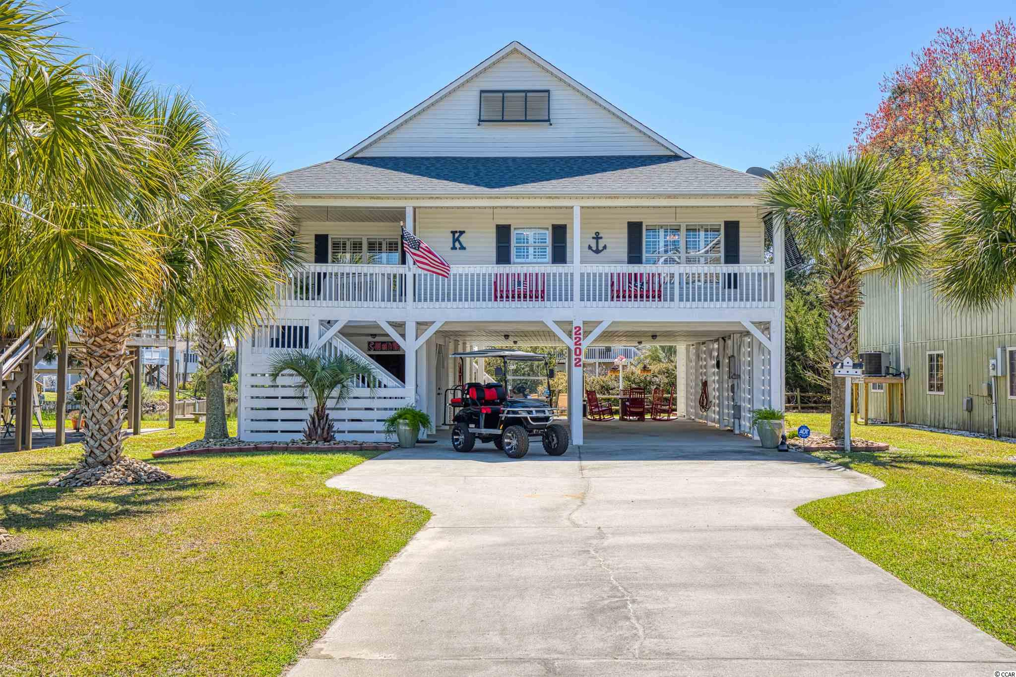 Looking to purchase the perfect beach home in the highly desirable area of Cherry Grove Beach? Here is your opportunity to own a turn key 3 bedroom 2 bath raised beach style home. The sellers of this beautiful home really put a lot into it and did not cut any corners from the landscaping, freshly painting the entire place on both inside and out, screening in the back porch, new A/C 2020, Dishwasher Jan 2020, Stove 2021, Fridge 2020, and brand new washer/dryer.  As you pull into the long driveway under the beach home you will find a nice size storage unit with built in shelves for all your tools, beach items, and even golf cart!  There is an enclosed outdoor shower behind the home as well as outdoor sink and grilling patio.  The home features Brazilian Cherry wood floors, a split floor plan, electric fireplace, granite countertops in the kitchen, a screened in back porch ( overlooking the beautiful pond), and plantation shutters.  Sellers put in a barn door in the master bedroom to access the bathroom and Bermuda shutters all around the home.  Too many updates to name!!! Grab your golf cart and take it less than a 5 minute ride to the beach!!