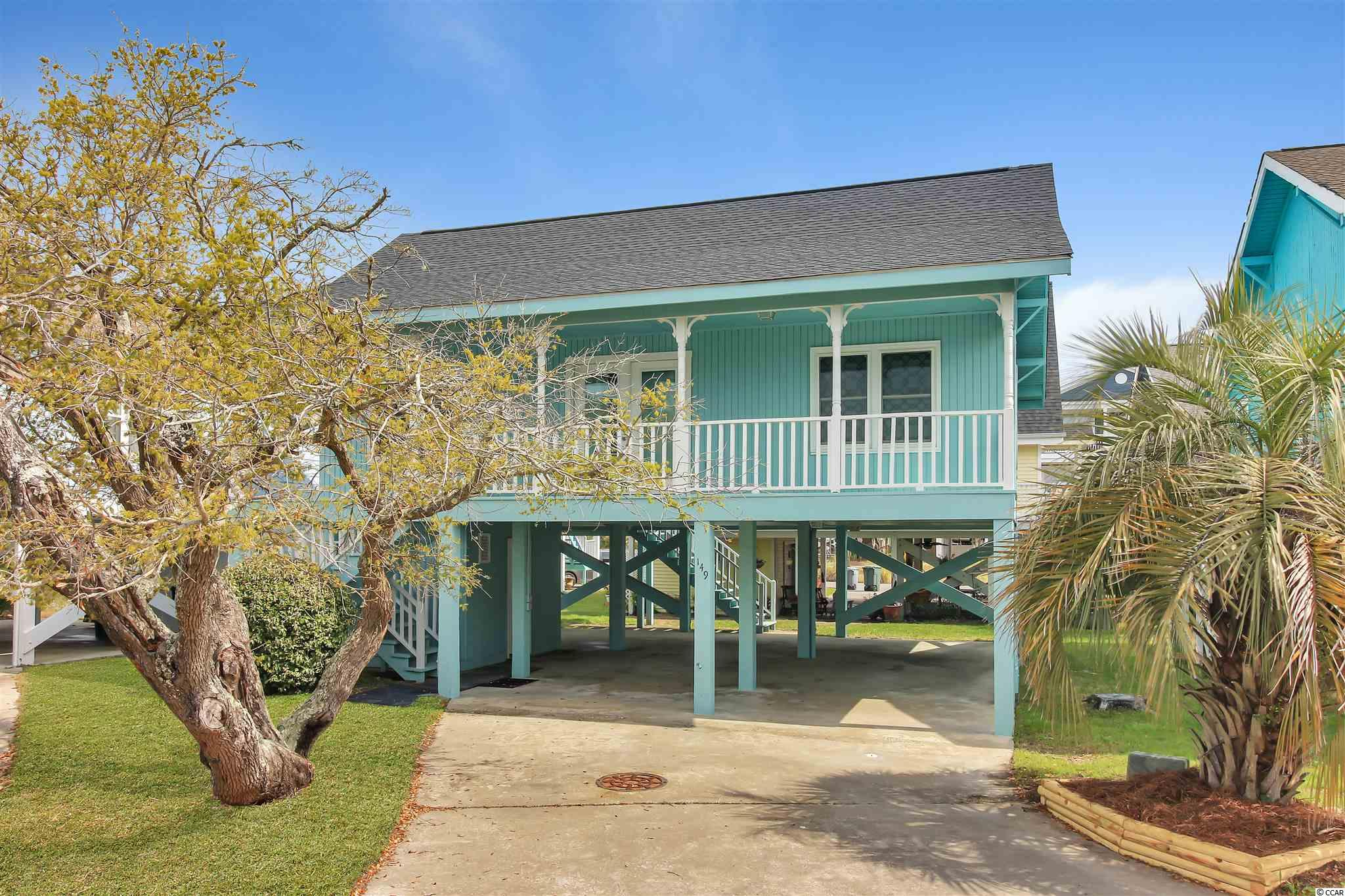 This Garden City Beach cottage is located just a stone's throw away from the beautiful Atlantic Ocean. You can even catch a glimpse of the Murrells Inlet Marsh from the kitchen and the back porch! As you enter from the front porch, you come in to the living area.  On the right side of the home, you have two bedrooms with a shared bath in between them. On the left side is the Master Suite as well as the Kitchen. The Master features an ensuite full bathroom for privacy. Downstairs there is plentiful parking and a great place to sit if you want to sit and eat in the shade and feel the ocean breeze, and an enclosed storage room large enough to house a golf cart.