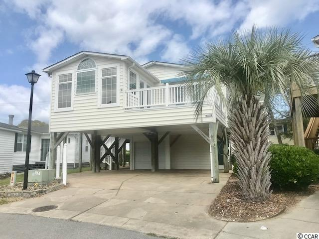 """This is truly a One-of-a-Kind home located in the""""Keys""""Section of Oceanside Village. Oceanside Village is a family friendly beach front golf cart community.  There is no better home for you to fill that """"bliss list"""" of must haves at a price and in a rental community that will allow you to continue to enjoy some of the finer things in life.   Featuring 4 bedrooms, 1 non conforming bedroom, jack & jill ensuites with adjoining showers on both levels, lots of windows for natural sunlight,and much more.  Wake up and enjoy coffee on the deck off the master suite that features a  sunsetter awning. Outdoors features multiple palmettos, crepe myrtles,stamped concrete, and  trex decking . This deck is perfect for entertaining, tropical drinks and ocean breezes, and beautiful views of the lake. This one of a kind home features slate tile throughout the downstairs, and much more Don't let this opportunity to own in one of the most sought after residential resort neighborhoods on the South Strand slip by. Come home to the """"Keys"""" for a lifetime of happiness.  Conventional Financing Available . Private Beach Parking"""
