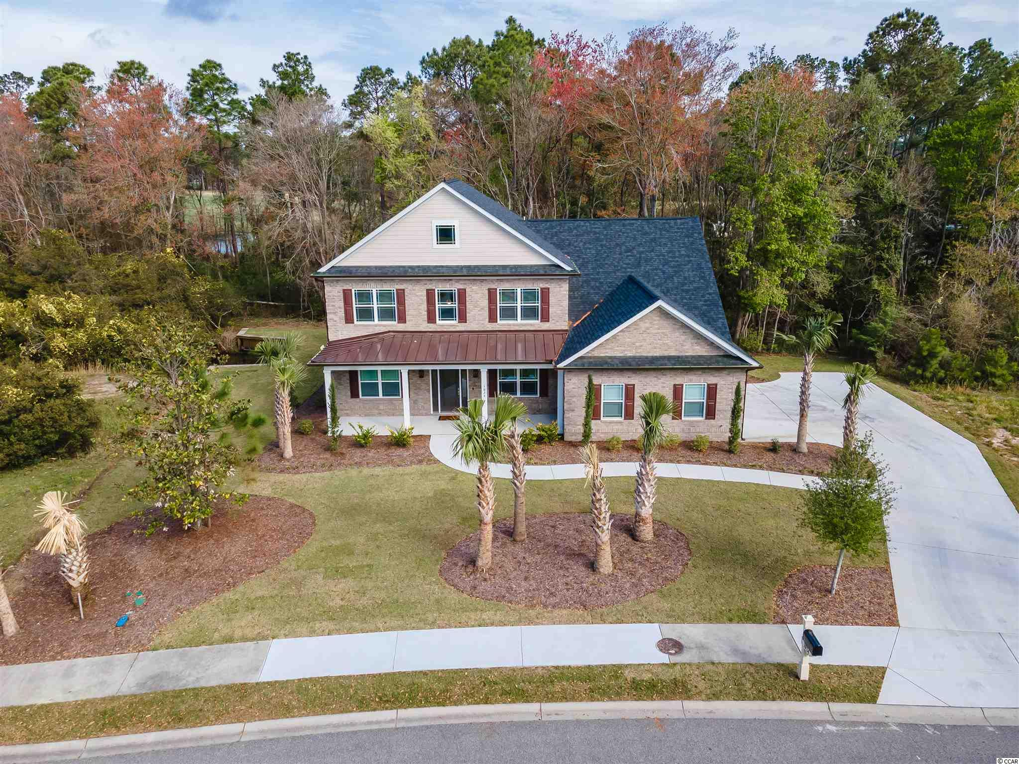 Don't miss out on this AMAZING all brick CUSTOM home in the heart of Wild Wing Plantation.  Built in 2020, this home features an open floor plan, water views, luxury vinyl plank flooring and custom finishes throughout.  The kitchen is a chef's dream with custom cabinets, granite countertops, double ovens, top of the line stainless steel appliances, and a huge work island perfect for gathering the family around.  Multi-glide sliding doors lead from the kitchen onto the screened in porch, overlooking the private back yard with water views.   The master bedroom features double tray ceilings, a walk-in closet, en-suite bathroom, and opens to the screened in porch.  The spa-like master bath has a walk in shower which features custom tile throughout, dual sinks, and a separate soaking tub perfect for relaxing after a long day on the beach.  The first floor also features double doors leading into a separate office space.  The upstairs has three oversized bedrooms, two full bathrooms and a bonus room.  The bonus room is the perfect size for a pool table and has a balcony overlooking the expansive lake views.  Wild Wing is a unique community which offers privacy, space, large lots and tons of amenities to its residents.  The community features a clubhouse, community pool, tennis courts, a playground and is a short ride to the beach and all the restaurants the Grand Strand has to offer.  This home won't last, schedule your showing today!