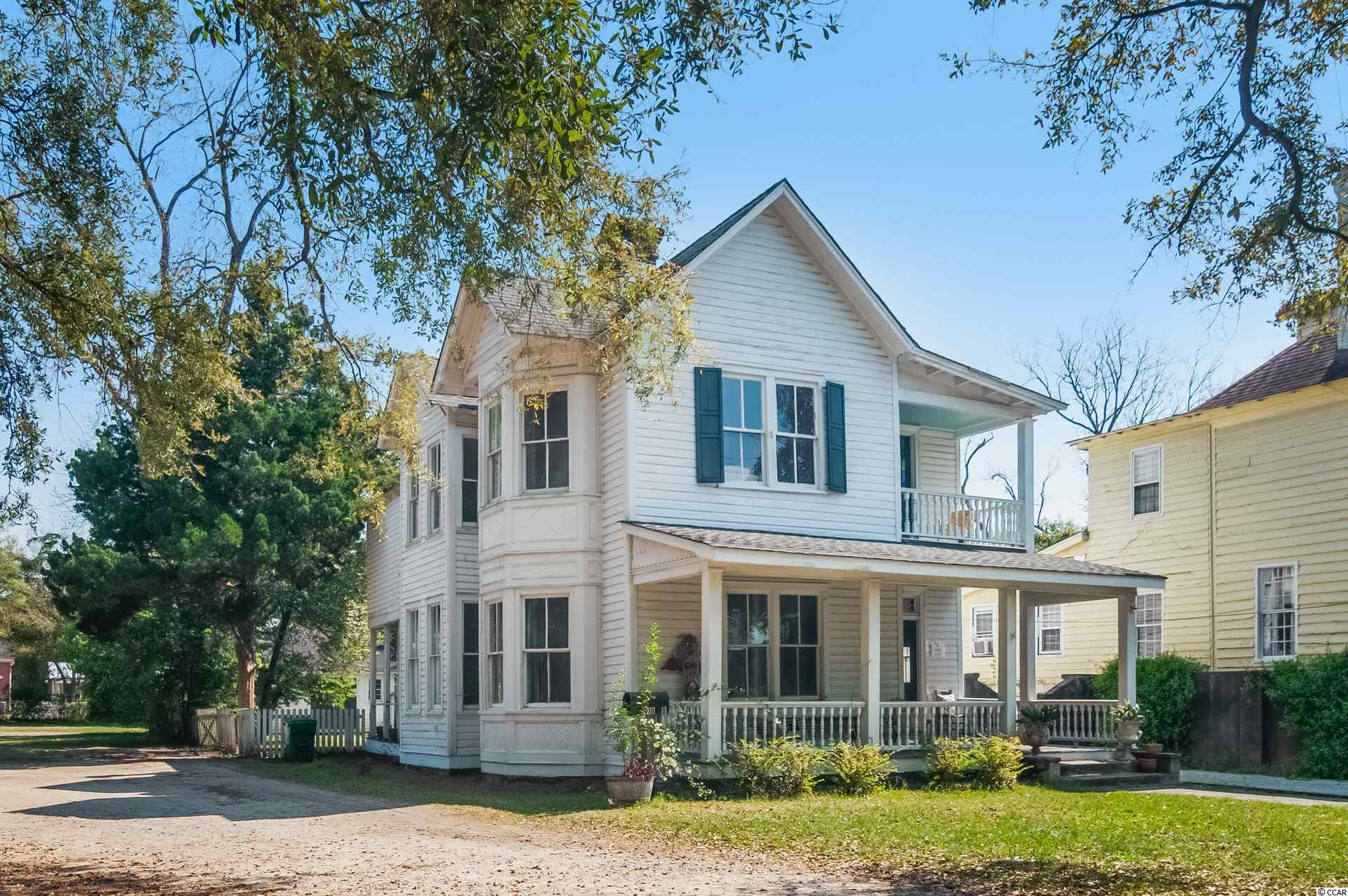 """Welcome to downtown Historic Georgetown SC.   This turn of the century home is located 2 blocks from the downtown shopping and dining district.    Upon entering the front door, you are greeted by a soaring two story entry hall.  Although the home is currently used as a rental, the rooms traditionally are a formal living room, formal dining, full bath, and great room on the main floor. A rear porch is meant to be screened,  Take not of period bay windows and fireplaces and the large amount of light.   Upstairs you will find two bedrooms that share a hall bath, a master suite .  Keep in mind that the second floor is also being used as an owners apartment.  Bay windows that mimic the first floor are also on the second. You will also find a charming """"dust porch"""". A common outdoor structure is the current laundry, but would make a fantastic outdoor kitchen and entertaining space.   At the rear of the property you will find a cottage that was relocated to the site from the neighboring property.   This house features a living room and kitchenette, one bedroom, and 1 bath.  This would be a lovely cottage to use as a short or longer term rental. Discover this classic home in downtown Georgetown!"""