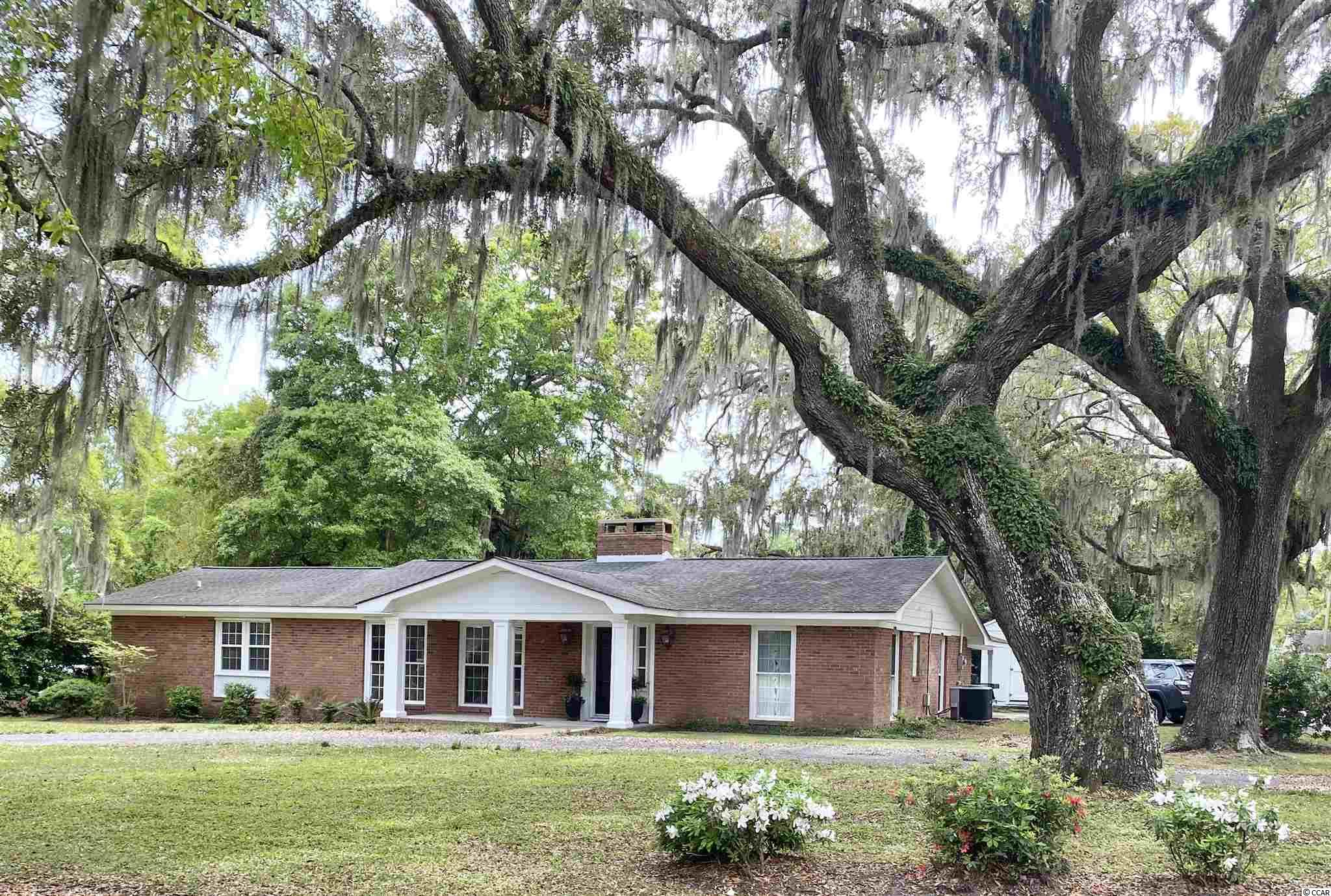 Charming Ranch home on .32 acre corner lot located in the heart of Murrells Inlet East of Highway 17. No HOA!!! Floor plan features large master suite (complete with walk in his & hers closets, master bath with double vanity, linen closet, jacuzzi tub, walk in shower,  & separate water closet), 2 guest bedrooms, additional full bath, living area with large wood burning fireplace and custom mantle, upgraded kitchen and breakfast bar, dining area and entryway den. Many improvements made by current owner include new roof, new LVP flooring, all new windows, rear patio addition, ductwork and HVAC, and kitchen remodel including solid wood cabinets, new appliances (cooktop, double wall ovens and microwave, dishwasher, and custom commercial style hood vent). Lot boasts several large live oaks, rear patio area, large detached 12x12 storage shed, carport, and enough parking for your boats, cars, and RV. Just a short stroll to local restaurants and the Murrells Inlet Marsh Walk.