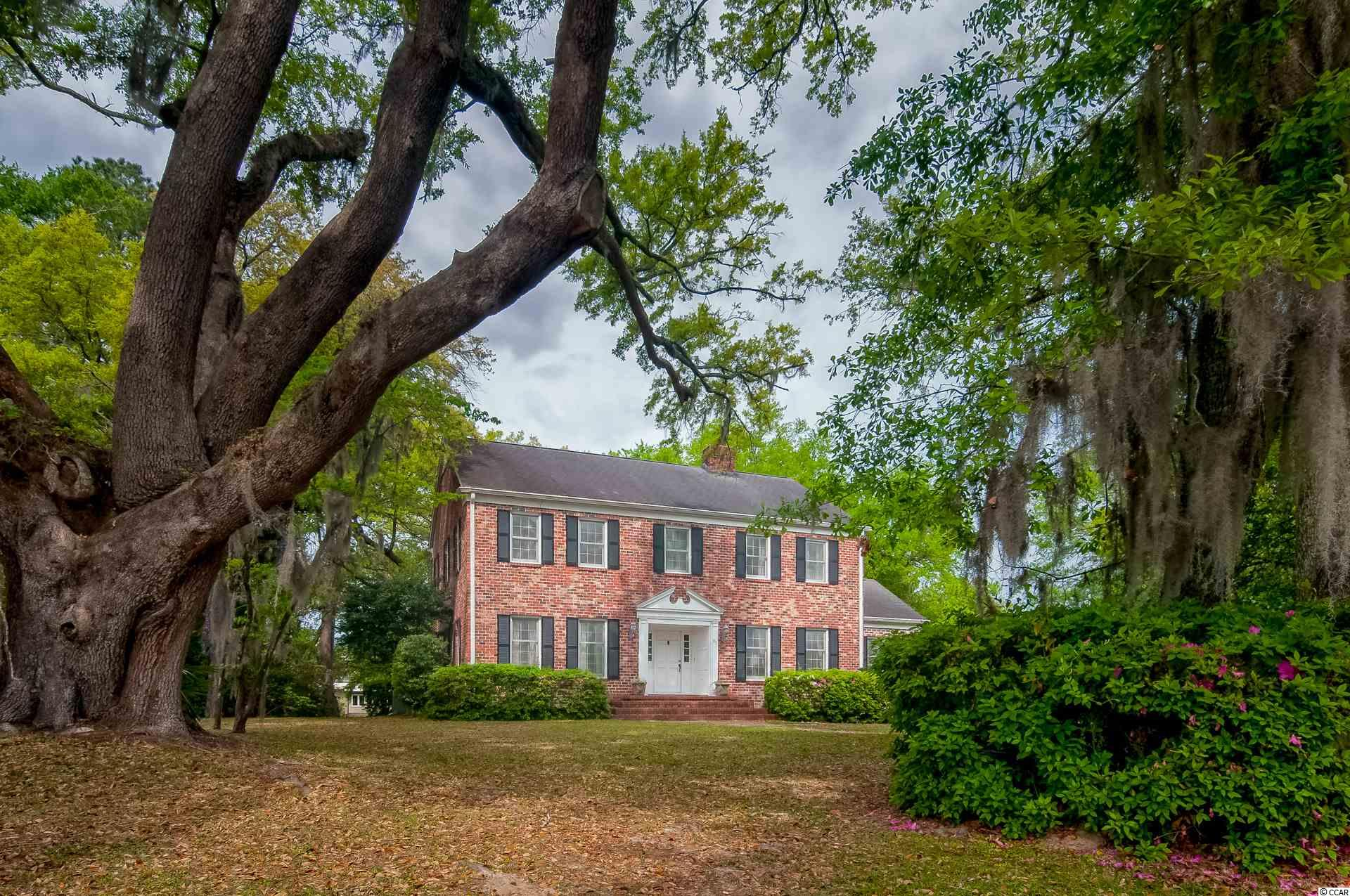 """Welcome to 97 Live Oak lane in beautiful Wedgefield Country Club.  This classic all brick Georgian home sits on a spectacular lot covered in a wonderful array of natural flora and fauna found in the area.  Upon entering thru the front door ,that is surrounded by a broken arch and pediment, you will find a lovely interior with entry hall, formal living room with wood burning fireplace, and a classic dining room.  The den, kitchen and breakfast room feature beams that were salvaged from a historic property.  In the den you will also find a wall of ballast brick that surrounds a second wood burning fireplace.   Walls in the den, the stairwell, and one downstairs bedroom are all covered in cypress boards.   Take note that a second downstairs bedroom opens onto a lovely screened porch overlooking the canal that leads to black river.   Upstairs you will find four more bedrooms and two more baths.   Loads of storage await in the closets and the attic space. Outside you will find a charming garage that favors a """"little red barn"""".     Enjoy the many amenities that Wedgefield offers!   Quiet streets, golfing, dining, and more!    Close to area beaches and the waterways of Historic Seaport Georgetown!   This classic home is being sold """"as is"""" but offer the buyer a fabulous opportunity for a large 'Forever home""""."""