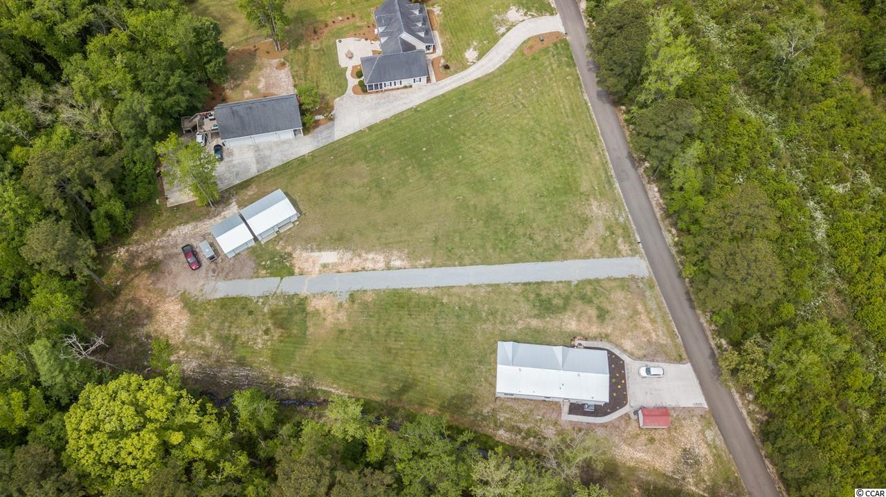 Don't miss this rare opportunity to live on 2.38ac nestled in a peaceful country setting with no HOA fees. This property features 2.38 acres of prime land in a semi-secluded, private road with no through traffic. It's zone CFA and it allows for storage of RV's, boats etc. Currently on the property there are also two garages (22'x30' and 22'x20') that will accommodate all of your storage needs and a 10'x16 shed. There also is a 1 year old farmhouse style home, with 2'x6' framing, that boasts 1832 sf with 3 bedrooms and 2 baths and large laundry room (available for sale but not included in the sale price) that could be used as rental income. There is also an already approved septic permit for additional 4 bedroom home. Conveniently located to area shopping plazas, restaurants, it's a few miles from the beach and close proximity to Murrells Inlet. A true treasure.