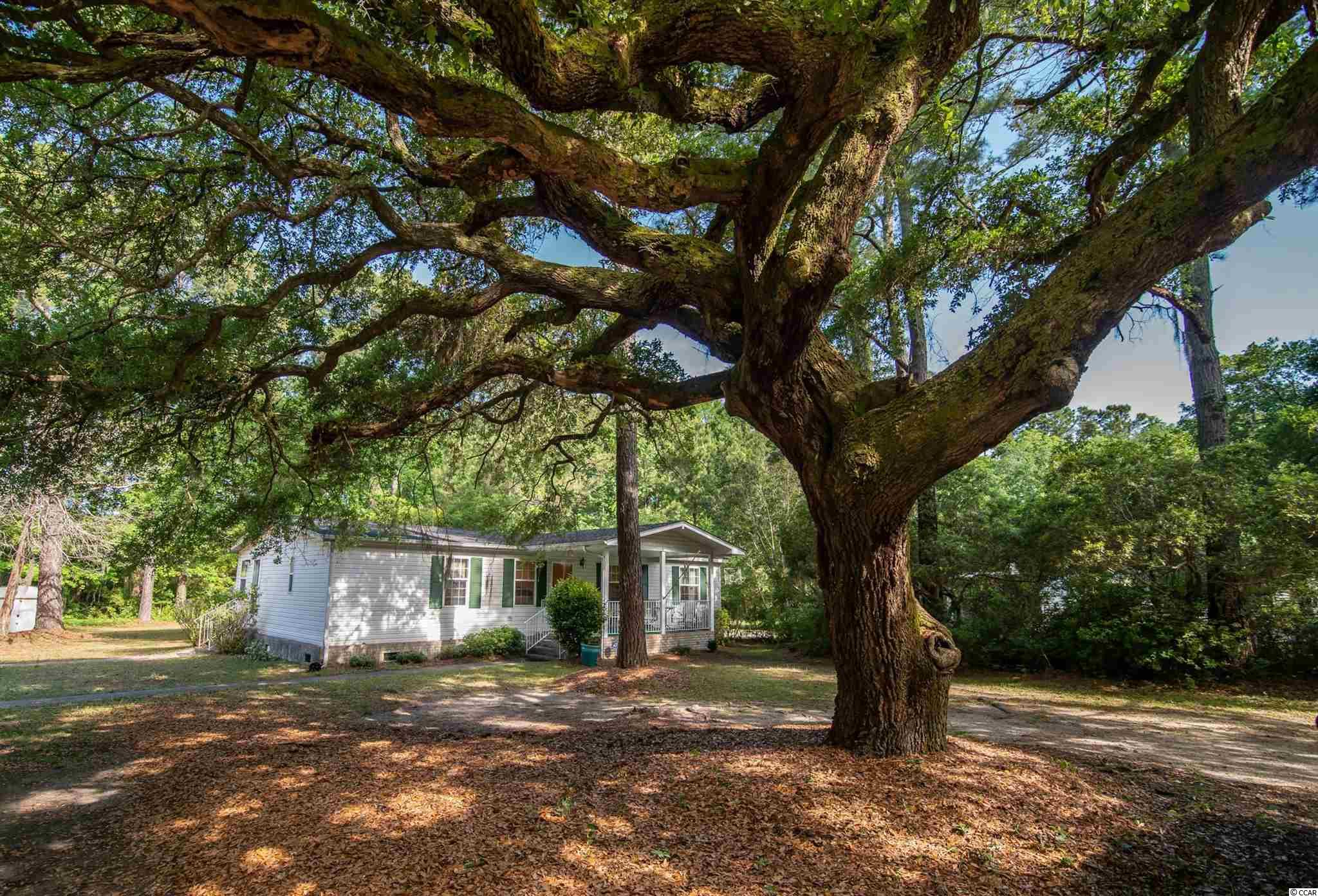 Three bedroom two bath home on one acre under a majestic live oak tree. This large shaded and wooded lot backs up to a pond. Well cared for home with newer roof and HVAC enjoys a covered front porch, screened back porch, and detached storage. Central location close to beaches, golf, and waterway.