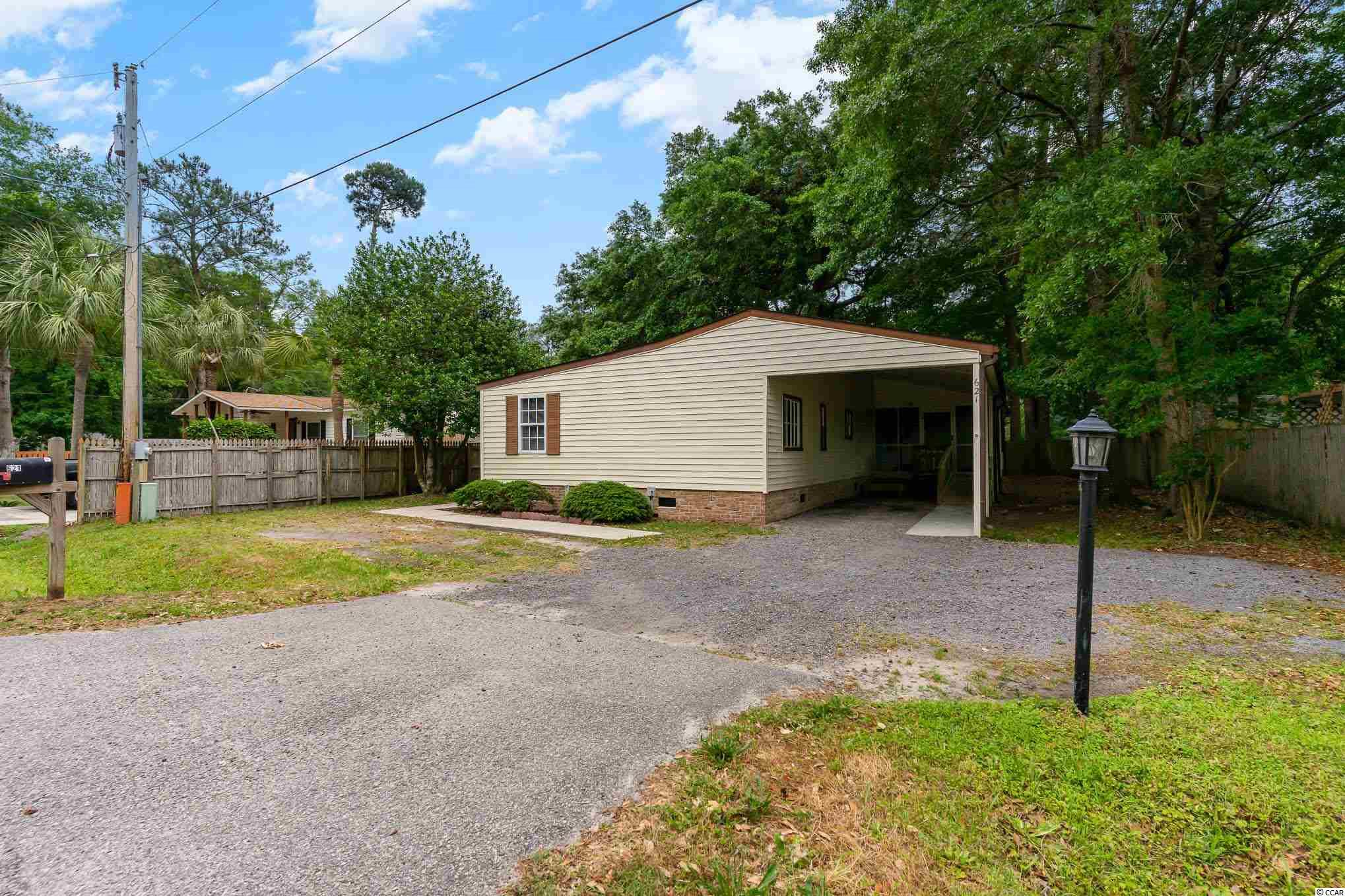 Best deal on the inlet! NO HOA! Walking distance to the famous Murrells Inlet Marshwalk and restaurants. This manufactured home has a private fenced-in yard, where you can enjoy watching birds while under the shade of a beautiful oak tree where you own the land! Take advantage of this opportunity with no HOA to bring your toys or create an income as an investment property that will offer your clientele the convenience of local restaurants, Brookgreen Gardens, Huntington Beach State Park, and Garden City Beach just minutes away. Enter the home with easy access from each side. This home boasts two covered porches, where you can enjoy your coffee in a peaceful setting. This home has 4 bedrooms with 2 full baths and a large open area that combines the kitchen and living area. Covered carport perfect for your cars, boat, or RV. Additional parking to the side.  Don't miss this opportunity to have all the benefits of Murrells Inlet with this property.   **Sold AS IS, Buyer to verify measurements
