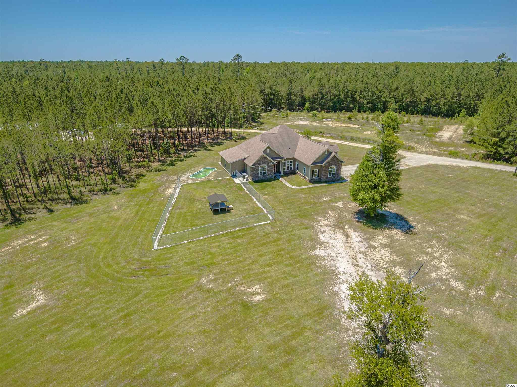 This 70 acre tree farm surrounds an amazing custom built home.  The 4 bedroom 3 bath private country home with in ground pool sits on 6 acres of cleared land and has 2 large buildings that are steps from the house.  A few of the features this custom home offers are solid surface countertops, coffered ceilings, built in cabinets with stone accents and storage galore.  The largest of the 2 buildings is 40x100, has 2 offices, a man cave and hanger doors to make bringing your equipment inside a breeze.  The second building is 24x36 with pass through garage doors. There are almost 2 miles of perimeter roads to ride ATVs or 4 wheel drive vehicles.  The wild life on this property is abundant.  The location of this home offers privacy while being only 20 minutes to the beach, golf and shopping.
