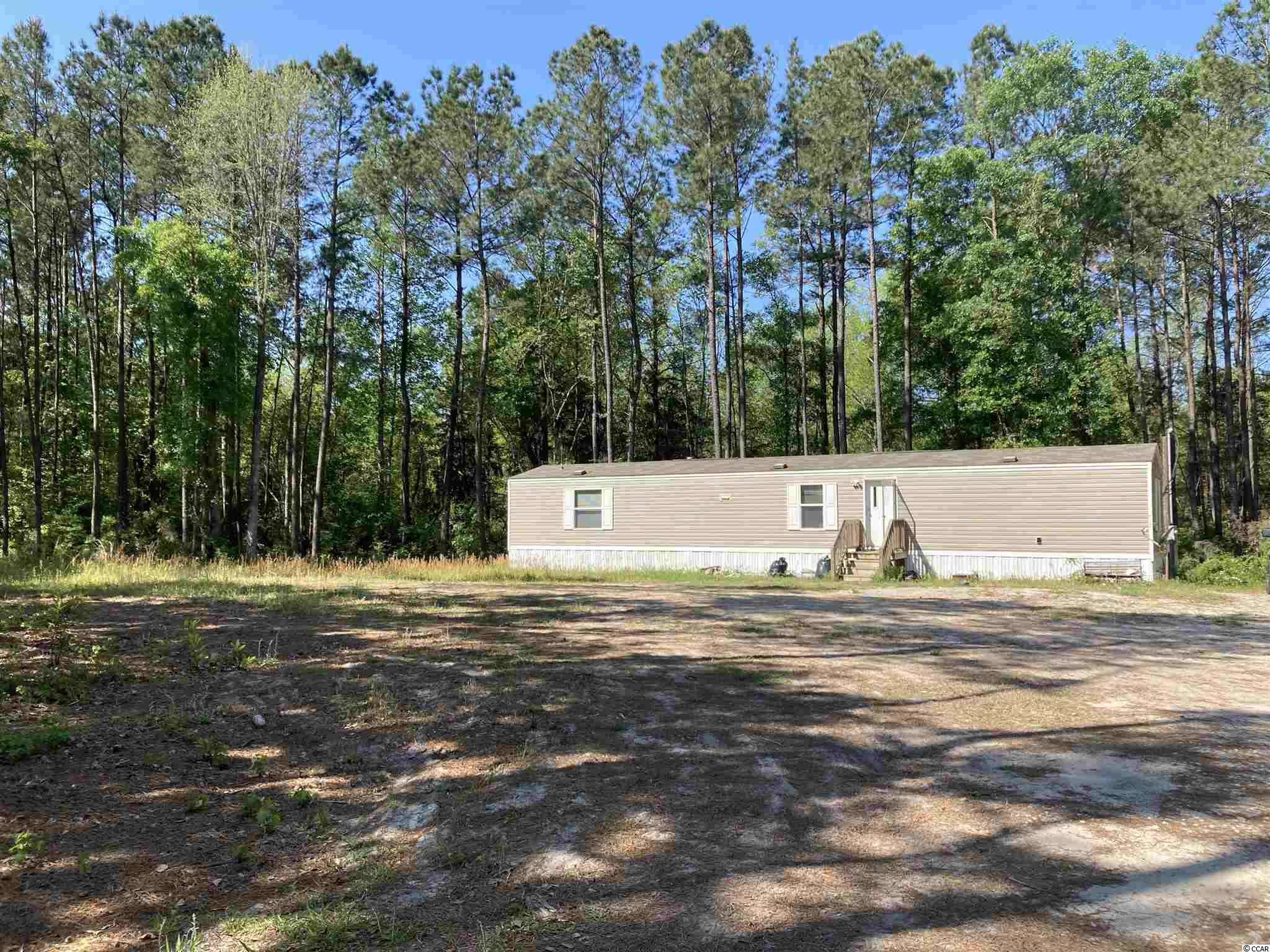 Very rare opportunity to own over 10 acres, a 4,500 square foot metal building and a singlewide all on one property. This property has so much to offer you have to see it in person to appreciate it. Outside the city limits but not too far. Only a very short driving distance to Myrtle Beach. NO RESTRICTIONS OR HOA!! Bring all your toys. Lots of room to play and then some. Call today!