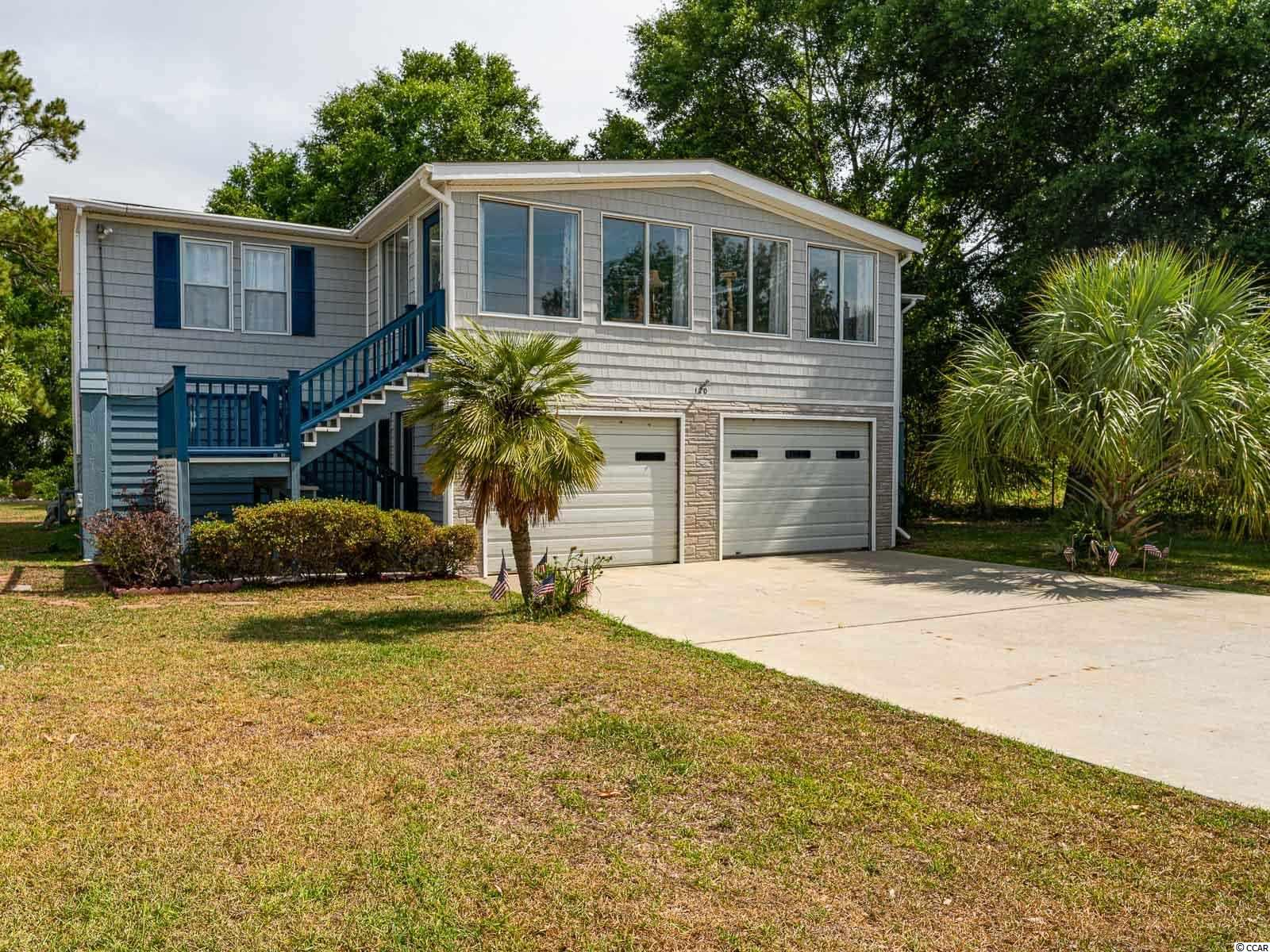 THIS is the perfect spot for Inlet living at it's best with the convenience of parking your boat/RV/Golf cart right at home!  This home is a manufactured home set up as a raised beach home in a quiet NO HOA community.  You can Golf Cart to the popular Murrells Inlet Marsh Walk with great restaurants, live music, and shopping!  Plus you have access to a public boat ramp at the south end of the Marsh Walk!  It is also just 4 miles to the Garden City Pier and beaches, as well as 7 miles to Brookgreen Gardens and Huntington Beach State Park!  There is a bedroom, walk in closet, and full bathroom with separate entrance on the ground floor perfect for a Mother in law suite, or college student living at home.  The upstairs main level opens into a bright and airy Carolina room with views of the Inlet.  Pass through the stylish sliding door to the open concept living room, kitchen, and dining room.  This house also offers a split bedroom plan with owner's suite on one side including en-suite bathroom, and 2 more bedrooms and full bath on the other side.  All 4 bedrooms offer walk in closets.  There is a spacious back deck with a patio underneath offering plenty of options for sitting outside and enjoying your quiet backyard.  Laundry as well as a large storage room is completely enclosed on the ground level adjacent to ample under-house parking for 3-4 cars with garage doors.  The driveway easily accommodates 4 more vehicles and the detached carports allow for RV/Boat/Golf Cart parking/storage with no restrictions.  The lawn irrigation system works by drawing water from the retention pond behind the house so it doesn't run up your water bill!  There is a handicap chair lift on the back deck steps as well as an elevator.  The elevator is not operational, buyer can either have it repaired or the neighbor is happy to remove it at no cost if buyer doesn't want it (the elevator was added on but did not have a building permit, owners used it previously, but have not used it in a f