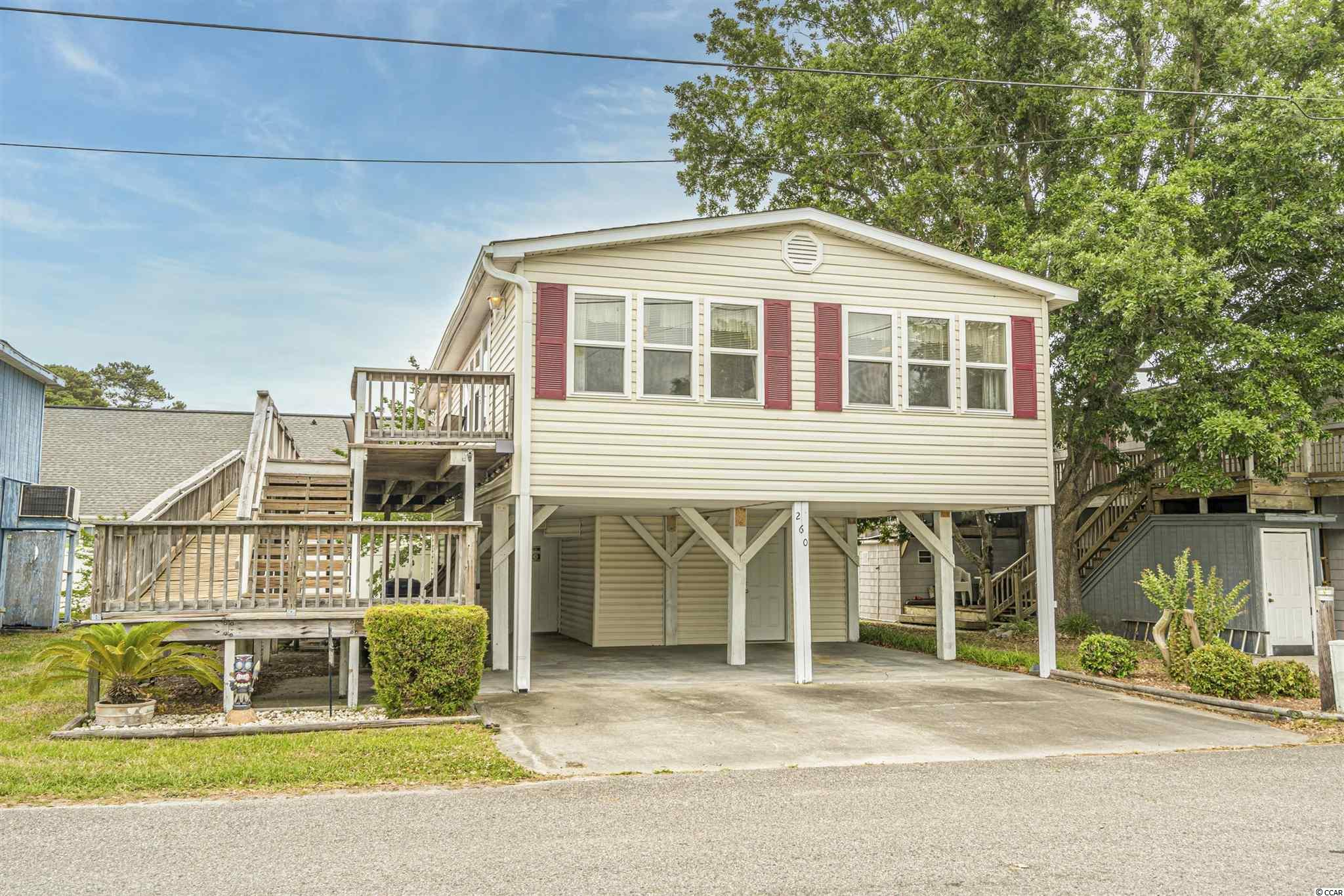 Enjoy easy living in this beautifully maintained beach home located in a gated, oceanfront community in Surfside Beach. As soon as you enter the home you will be pleasantly surprised by the spacious interior that flows effortlessly throughout the main living/dining areas. This open layout is ideal for entertaining guests and/or vacationing comfortably with larger groups. The eat-in kitchen has a breakfast bar with seating for two, quality like-New appliances, and comes complete with all kitchen essentials. The bedrooms are cleverly concealed in the rear of the home allowing for privacy away from the main areas. Updated Laminate-Wood Flooring, Freshly Painted interior, New Roof, and Like-New HVAC and Water Heater. Soak up the sun or relax with a good book on the deck- Deck is equipped with an access ramp to the 2nd story. The underneath of the home has a large storage unit for all the extras and room to park 4 vehicles comfortably. Established Turn-Key weekly rental home, offered fully furnished and tastefully decorated. Walking distance to the beach in the Oceanside Village community. Homeowners and their guests have access to resort-style amenities including indoor/outdoor pools, kiddie splash zone, tennis/basketball courts, dog park, playground, fitness center and private beach access with parking and an Oceanfront Restaurant. Schedule your showing today.