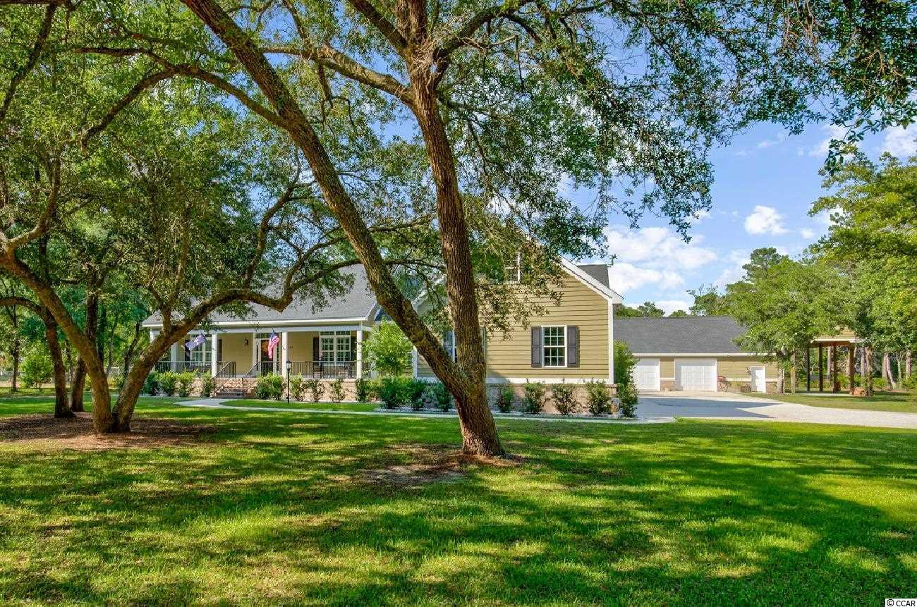 """30 Live Oaks and lush landscaping adorn the one acre setting for this builder's Lowcountry home with a saltwater pool. The exquisite residence features 3 bedrooms all on one level and a large bonus room over the 2 car garage. Perfect for the those who love the great outdoors, the additional detached 2 car garage features a heated """"man cave"""" and a huge bay for your big boat or RV. Located in the River Road neighborhood, where there are no HOA fees, 165 Half Moon Trail welcomes you with a large front porch. Open the door to the foyer and see straight through the living room to the back screened porch overlooking the pool. The perfect kitchen looks like it came right out of a magazine, is open to the spacious dining room, and features stainless steel appliances and quartz countertops. The master bedroom features two walk-in closets, two separate vanities, private water closet, linen closet, separate garden tub, and a large porcelain tile shower. When you buy a builder's home, every detail has been scrutinized. Ask your Realtor for the spec sheet available in the MLS listing. Some of the features include: concrete slab in the lighted, encapsulated crawlspace, 2 x 6 wall construction, Hardy board exterior, powder coated aluminum railings, spray foam insulation, Brazilian cherry flooring, plantation shutters, and an electric fireplace that looks like gas, but without the need for propane. The pool furniture conveys. Pawleys Island, one of the oldest summer resorts in America, is located about an hour north of historic Charleston and 30 miles south of the Myrtle Beach Airport. Pawleys Island is known for its shoeless, carefree, laid-back life style, which includes fishing, crabbing in the creeks, ghost stories, rope hammocks and a beautiful stretch of wide, sandy beach. On the mainland, you'll enjoy a variety of shopping, dining, golf, excellent schools and award-winning health care facilities. Full time or part time, Pawleys Island is a great place to live!"""