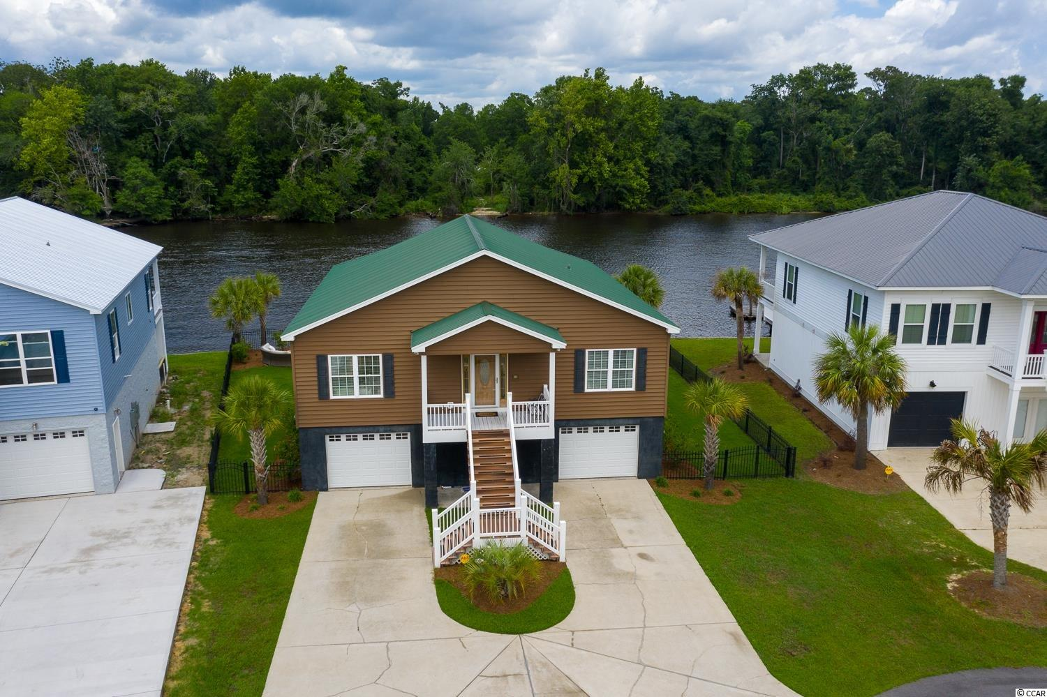 HUGE opportunity to enjoy all that waterway living has to offer in this beautiful 3 bedroom 3 full bath home with No HOA located directly on the intracoastal waterway with incredible views ! You are minutes from Market Commons where there is shopping , dining and entertainment galore. This home boasts lots of parking and storage for all your boats, jet skis, RVs etc. It has its own private dock and is ready for sipping coffee watching the boats go by! Do not miss this home with granite countertops, wood flooring, stainless steel appliances, tray ceilings, spacious bedrooms and a masterful master suite overlooking the waterway. The porches and patios make for the perfect spot to grill out and entertain. The kitchen is gorgeous and all common rooms face out over the water! The first floor is perfect for a guest suite, a man cave , or a recreation room with it's own private bath and entry to the outdoor oasis! DO not let this one pass you by !!