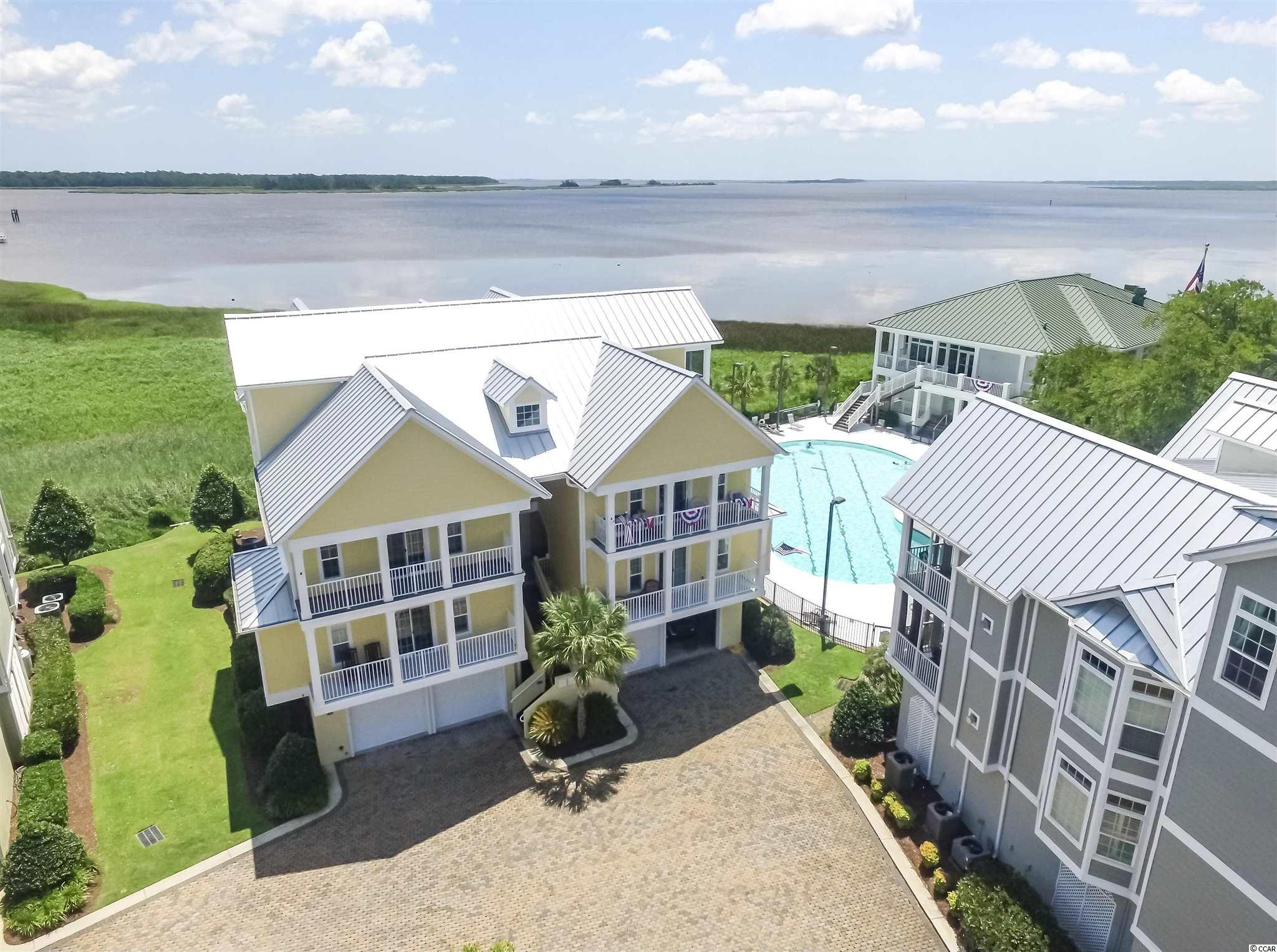 Welcome to Marina Village in Georgetown's beautiful Belle Isle Yacht Club community. Don't miss this well-appointed 3 bed / 2 bath waterfront unit with panoramic views of the Intracoastal Waterway and Winyah Bay. Enjoy sunrises over the bay from your screened porch and watch the boats pass by throughout the day. All bedrooms are located on one level and the unit is accessible via stairs or elevator. The kitchen features high quality cabinetry, stainless appliances and granite counter tops. There's also a wet bar in the living area for mixing an evening cocktail or entertaining your guests. The master bedroom overlooks Winyah Bay and has a spacious bath with dual sinks, a tiled shower and a jet tub. Owners will also appreciate the huge garage space with plenty of parking and storage. Other features include a gas fireplace, plantation shutters, crown molding and hardwood flooring in the living room and master bedroom. Community amenities include the yacht club, swimming pool, a private beach house on Pawleys Island, tennis courts and a full service marina that is now taking reservations for boat slips. This property would make a lovely full-time residence or an ideal weekend retreat for fishermen and boaters. Book your showing today to view this wonderful waterfront property.