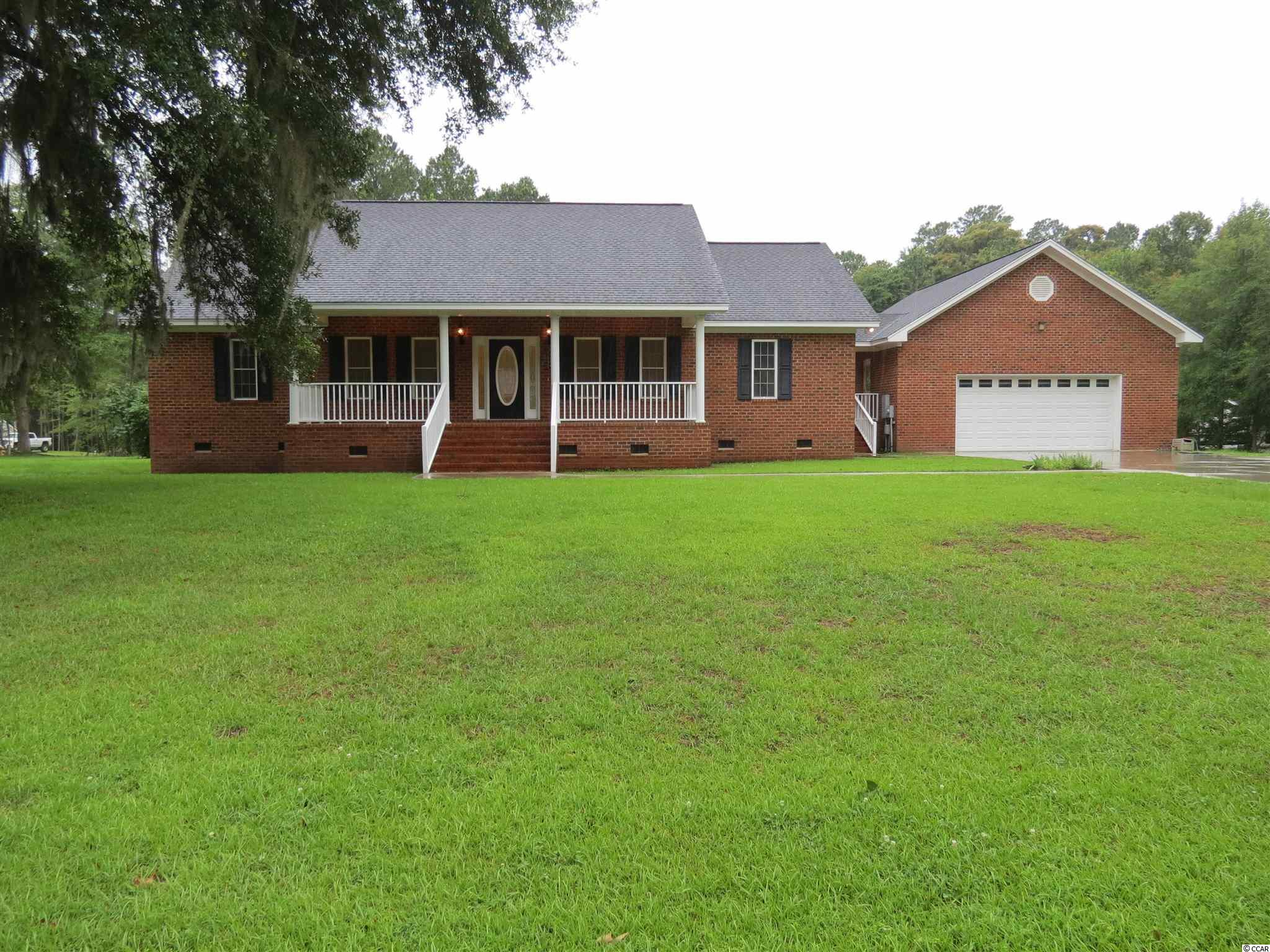 What a beautiful Lowcountry style all brick veneer home, single level, open floor plan, breezeway to a 2 car garage that has front and back loading capability and located on a spacious one acre lot. Tile floored front porch enhances the beauty as you enter the tiled entrance way that reveals a pocket door office, a formal dining room and a vaulted ceiling living area. Tiled floor kitchen with white cabinets, double ovens, smooth top range, GE refrigerator, recess lighting, breakfast bar plus breakfast nook with bay window. Oak hardwood floor Living area with gas log fireplace, 14 ft height ceiling, 2 ceiling fans and recess lighting. Oak hardwood floors in all bedrooms, tile floored baths, double walk-in closet in Owners suite, three storage closets with shelving in tiled floor laundry room. Other features include a 15.10x 11.9 screen porch, built in gun cabinet, irrigation system on a 85 ft well, 2 car garage measuring 29.3x31.3 and a back patio area.