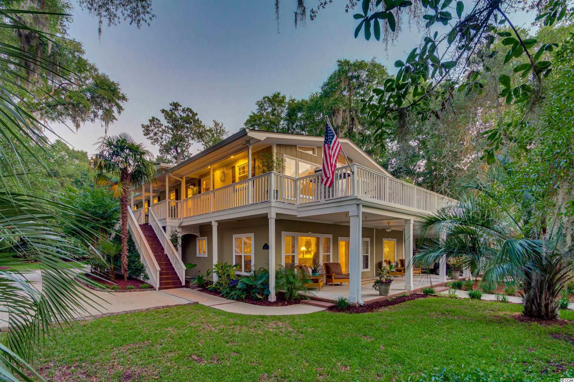 Priced BELOW recent appraised value.  This beautiful 2 story home actually has a shared deepwater dock located right on the ICW, Waccamaw River.  It's literally just a short walk from the house. The 20x30 covered dock which has two separate boat lifts  and floating docks, one for each owner, and plenty of space to dine or lounge right on the dock. The dock is great for fishing, water sports, and exploring the creeks that meander through the old plantation ricefields.  Maybe you just want to lounge out there observing all the local wildlife you might see or watch the most beautiful sunset or gaze at the crystal clear stars.   This low country beach-style home, decorated beautifully with all the charms of southern living, feels like living in a tropical oasis. There is a circular driveway with crushed stone. The lush landscaping hosts banana trees and elephant ears, palms, crepe myrtles and so much more! The welcoming low country stairs has a hidden outdoor shower behind them. The views are incredible and the homeowners designed them so they can be appreciated from many different perspectives. There are wrap-around porches and a screened-in porch nestled amongst live oaks covered in Spanish moss.  The homeowner's design reflects their love of nature and the comforts of life. They wanted their property to feel welcoming yet private. The two stories design is suitable for so many. Each level has its own family room, kitchen, master bedroom, and laundry which is perfect for year-round residents welcoming guests, a multigenerational family that all want to live together yet love their privacy, or maybe just two separate families.  The spiral staircase connecting the two could be replaced with an elevator if needed. Upon entering the home, anyone will be impressed by the pecky cypress beams and whitewashed walls which lend to the low country feel. This house is like a hidden treasure of well-thought-out and designed southern charm around every corner.     You'll want to to
