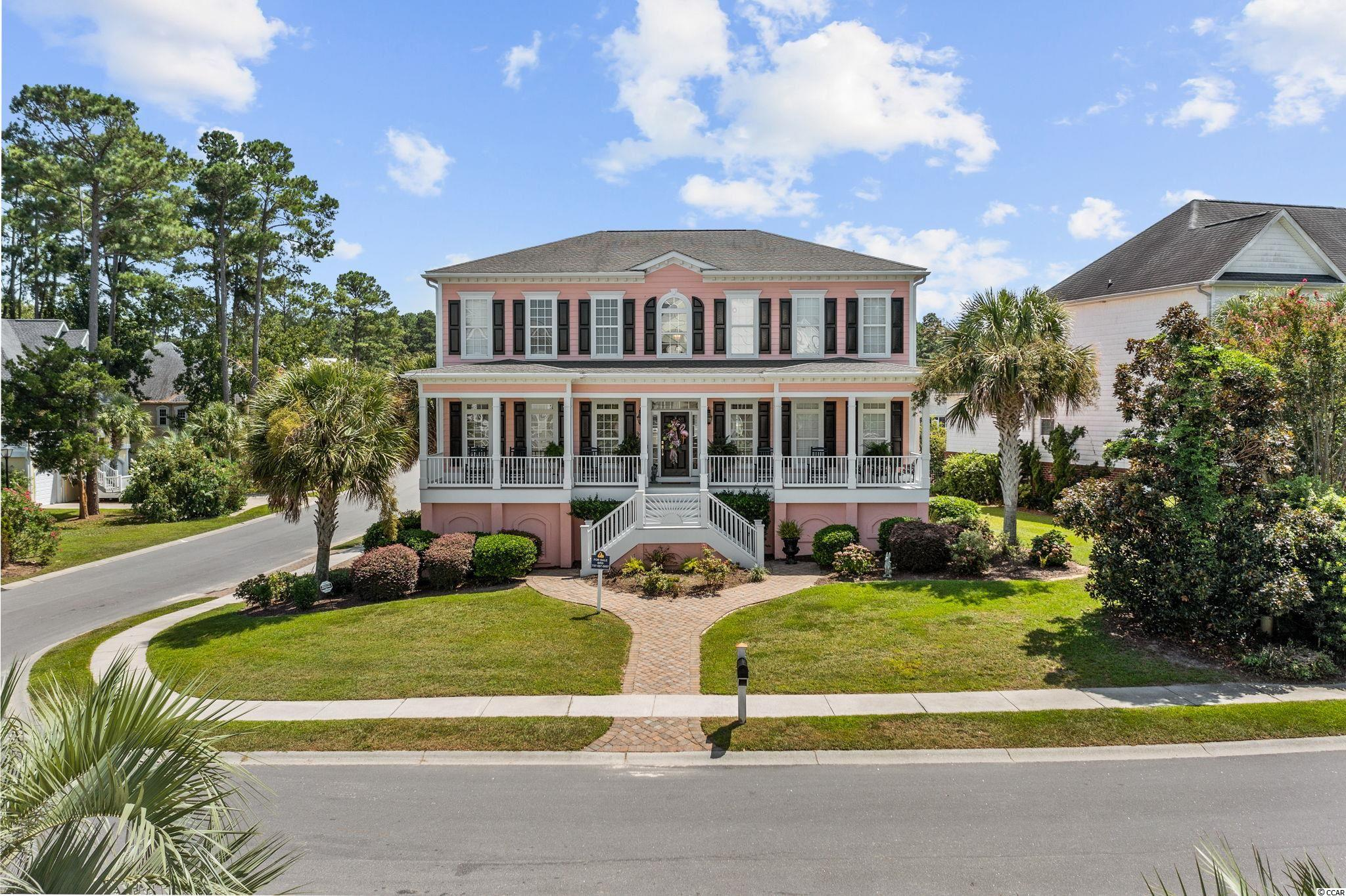 """Stunning low country styled home located in the prestigious Intracoastal Waterway community of Sunset Harbour.  This traditional charmer sits just across the street from the waterway and offers owners the best of the coastal lifestyle.  Full waterway view from the front porch, enjoy spending the evening watching the boats go by.  A large front porch welcomes guests and invites you to sit and stay a while.  Inside you will find soaring double height ceilings in the foyer and living room with an open staircase to the second floor.  This home is perfect for entertaining with a formal dining room and large chef's kitchen.  The kitchen features ivory custom cabinetry, stainless appliances and granite.  There's plenty of counter space to prepare meals for gatherings or a large family.  A breakfast nook and a spacious sitting area with a sun room feel are all open to the heart of the kitchen; perfect for a """"gathering"""" spot. The custom details and finishes of this property are plentiful.  Dark cherry stained hardwood plank flooring, extensive mill work and substantial crown moldings can be found throughout.  Smooth ceilings, recessed lighting, lever door hardware and main floor built in speaker system are other features that should be mentioned.  Freshly painted interior trim and walls in a neutral color pallet.  The home is bright and filled with light.  The living room has a double bank of windows spanning floor to ceiling to create an open feel.  For those chilly nights, a gas log fireplace can set a warm tone in the home.  The main floor owners suite opens onto the rear deck for private relaxation.  The en suite bath is inviting with dual vanities, custom cabinetry and granite counter tops.  Large walk in closet with separate water closet, walk in shower and large garden tub finish off the space.  Tile flooring in a neutral ivory give the space a bright feel.  The master suite is painted in a soothing and cool blue tone that have a decidedly spa like feel.  Upstairs, yo"""