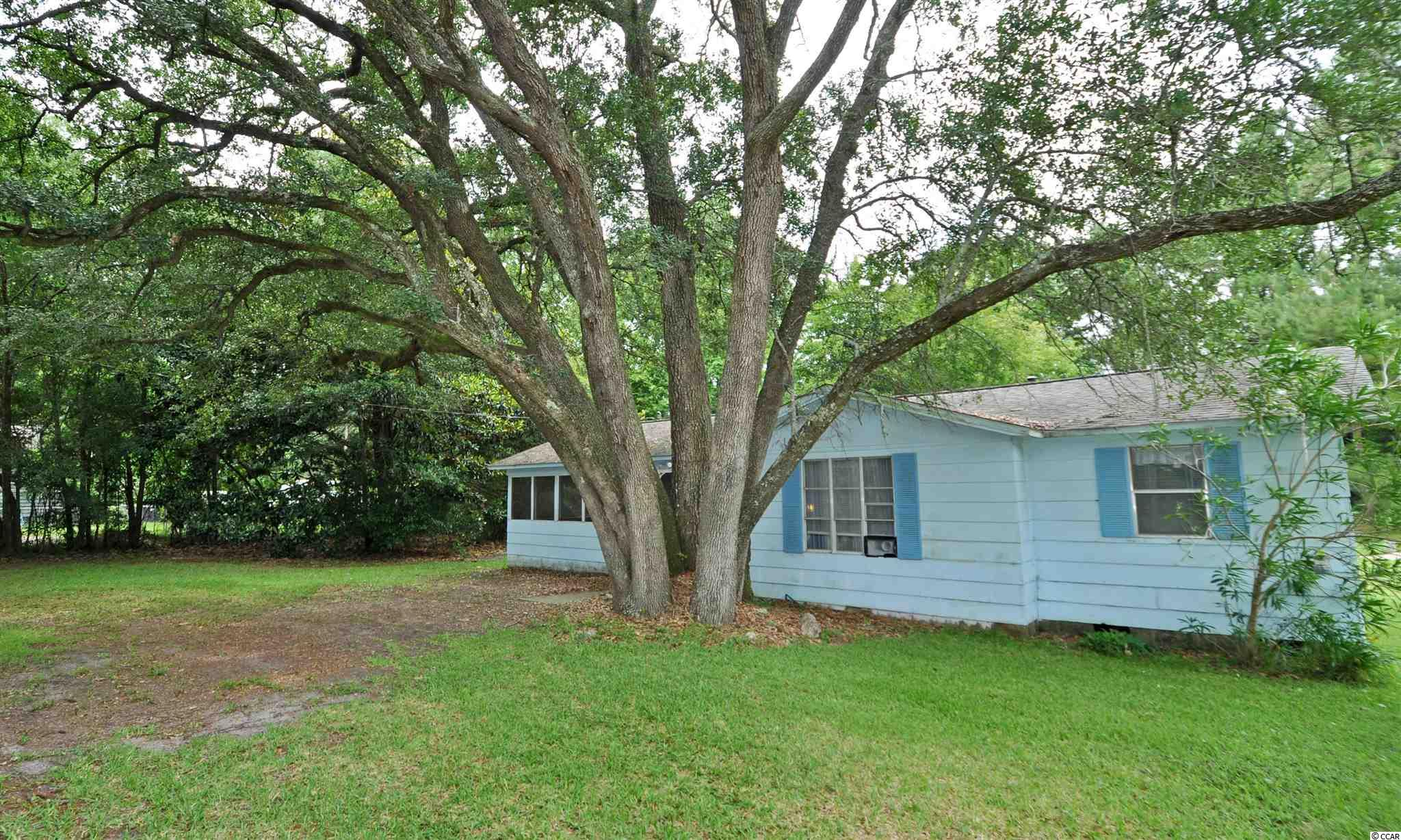 This is the quintessential Southern cottage, an appealing light blue color, instant charm and movie-script landscaping with its signature live oak and impressive mature magnolia trees and set back on a wonderful, over-sized lot for privacy and innumerable-use-options.  This attractive 3 bedroom/1 bath residential home on a large, half-acre-plus property is secluded but is conveniently located near many businesses and is in the desirable Hamlet of Little River, Horry County's second oldest town, which is renown for its proximity to the Atlantic Ocean via the ICW and rich nautical history including being a notorious, popular pirate port. For boaters, there are several marinas nearby to buy or to rent boat slips. For golfers, there are numerous signature golf courses, plus restaurants, antique and thrift trails, recreation, shopping, access to major highways and medical services, and good schools and parks. It adjoins North Myrtle Beach, which was recently named one of the safest cities in the nation and with one of the best beaches in the U.S., the nearby Cherry Grove Beach, minutes away. However, taxes are levied at low, low Horry County rates. View this inviting, well-priced rustic charmer with magnificent indigenous landscaping for a personal residence, rental or with potential for investment. As it is located near the casino boats, great restaurants, the historic district with its own legendary live oaks and the riverfront/Intracoastal Waterway where development is expected and may include a fishing-village-inspired concept with marshwalk and a marina. This is a spacious lot, and the cottage itself immediately beckons with a coveted wrap-around screened porch and lots of room to comfortably park cars in the designated tandem front-yard entry. The yard itself, of course, is equally appreciated, for its grand square footage and possibilities. Bedrooms are unexpectedly spacious, too, and have notable closets; and there is a larger jack 'n jill bath which is modernize