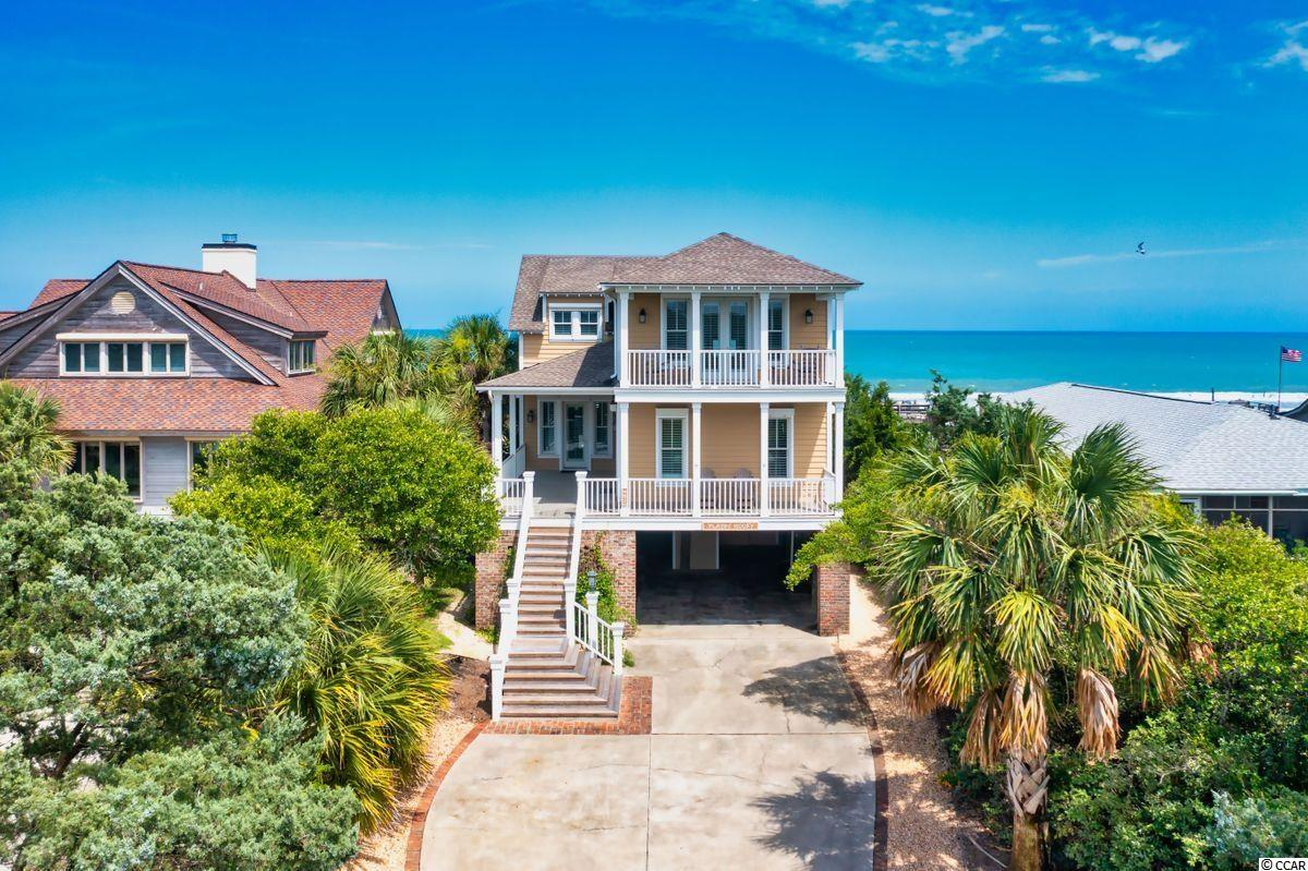 If you're Playin' Hooky do you want to be on the beach or the creek?  Why choose when you can have both!  Located in a prime, oceanfront mid-Island location of Pawleys Island's Historic District, this striking beach house is graced with a healthy dune system on the oceanfront and lush coastal views, and the opportunity to wet a hook on the creekside! While Mother Nature has provided the most irreplaceable amenities, this Wayne Rogers-designed home is built with quality craftsmanship and features befitting of a comfortable coastal lifestyle for year-round or vacation living. Careful not to miss a single spectacular view, each room offers a different vantage of the beach, ocean, or Pawleys creek and the porches on both sides offer ample opportunity to soak it all in! The main level of the home offers a sprawling open floorplan centered by a well-appointed kitchen with a Thermador cooktop, double oven, fabulous counter space, and prep areas.  The living and dining areas are open to one other (perfect for family get-togethers!) and are nicely warmed by an impressive fireplace flanked by built-ins. Finishing the main level of the home is a large laundry and home management center, powder room, and a creek view bedroom with en suite bath. Up the stairs is the 2nd-floor den and 4 additional bedrooms. The primary suite is on the oceanfront with a private porch overlooking one of the most uncrowded areas of Pawleys and a spa-like bath with an oversized shower and soaking tub. The creekfront suite has its own balcony with a gorgeous perspective of the creek, marsh, and even Pawleys Chapel!  This 5 BR, 4 1/2 BA home is upfitted with a hurricane protection system, GeoThermal HVAC, central vac, and a three-level elevator making it one of the Island's most efficient homes. It also boasts heart of pine floors, pecky cypress paneling, a sun deck that wraps around to screened outdoor dining, a double outdoor shower, and changing room making for a home reminiscent of Pawleys' yestery