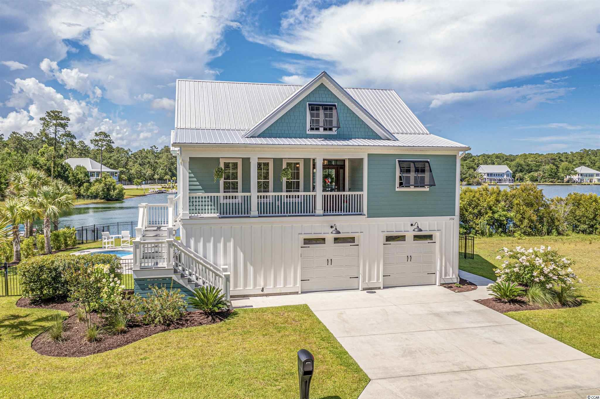 Rare gem, a modern coastal oasis on pristine, private lake! Who said you can't have it all? Live, work, entertain, and play in a custom built, modern coastal style house on a 20-acre, spring-fed lake located in a private gated community only minutes from Murrells Inlet's famous Marshwalk, Huntington Beach State Park, and Brookgreen Gardens! Only two years old and meticulously maintained, the owners created an oasis with high-end furnishings in a fusion of raised beach style and mid-century modern design. Spectacular lakeside living with a private dock, in-ground pool, hot tub, and endless outdoor entertainment possibilities with enough seating to easily accommodate 28. The lake views from the upper level kitchen, great room, and screened porch are simply breathtaking! Nine foot ceilings and crown molding on both levels, the great room on the upper level features a dual tray ceiling, luxury vinyl flooring, a custom shiplap accent wall, and more. The kitchen is stunning with quartz countertops, stainless steel appliances throughout, custom cabinetry plus, so much more. Propane tank for the kitchen's cooktop and an outdoor grill. Wait to see the custom laundry room where everything imaginable has been added for high utility use without compromising aesthetic and design! The lower level features two guest bedrooms, one with a built-in Murphy bed and workspace. The other guest bedroom and the large flex space with kitchenette overlook the lower porch and lake. The large, finished two-car garage has additional space for a golf cart or for extra storage. This home was built to last with exterior HardiePlank siding and a metal roof for durability and energy efficiency. You will be impressed with the condition and many upgrades on this turnkey, move-in ready, fully furnished property. Schedule your showing today!