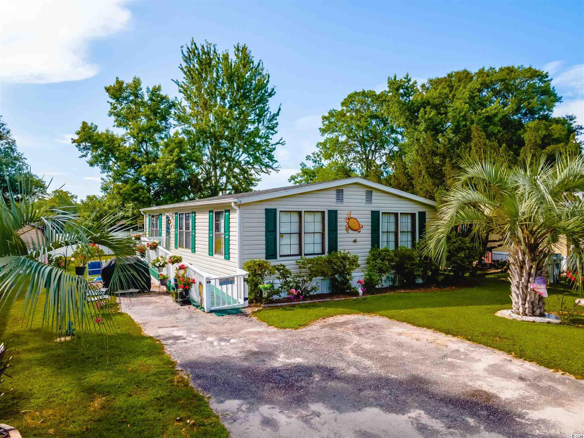 Cozy Double Wide now available in the Captain's Cove Community! Just a few miles North of Pawley's and a Stone's throw to the Marshwalk & Huntington State Beach, this is the best location on the South End of the Grand Strand. This charming home features 3 bedrooms, 2 bathrooms and 1,400 sq ft of indoor living space and tons of of outdoor living potential. The floor plan features an open kitchen and living room space, high ceilings, bright windows and durable vinyl flooring that resemble hardwood in some rooms. The kitchen comes equipped with bright white appliances, wooden cabinets, plenty of counter space, and a very spacious laundry room. This cottage style double wide also boasts high ceiling beams and a split bedroom and bathroom layout for the convenience of out of town guests or multigenerational living. During the summer, entertain in style on the side deck or relax near the sparkling community pool or head to the Inlet and grab a bite to eat at one of our many Water Front Dining Experiences. This home also comes equipped with a 2 car parking space for private off street parking. Appliances to convey with purchase of the home! Located in the highly coveted Coastal town of Murrells Inlet-It won't last long. Call today to schedule an appointment to come see it! (Captain's Cove is a 55+ Community) {Motorcycles & Pets Allowed, but no rentals}