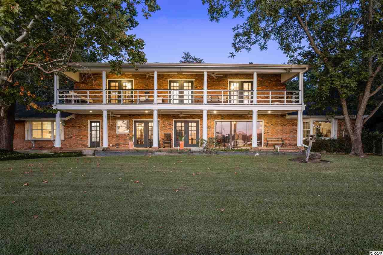 This beautiful waterfront home features double porches overlooking the Sampit River and is located just minutes from the INTRACOASTAL WATERWAY and Winyah Bay. Situated on a large double lot, you will be amazed by the stunning views and cool breezes. Enjoy the amenities of the nearby East Bay Park (such as a public boat landing and kayak launch located just a few blocks from the home) or take a brief walk to downtown restaurants and shops as you relish life in this charming historic town. This home is perfectly appointed for entertaining with over 4800 SF of space for you and your guests. The large entrance foyer is flanked on either side by an oversized dining room and a formal living room with a fireplace. The informal family room has a gas fireplace and sliding glass doors leading to the porch. Next to the family room is the downstairs master suite with double walk-in closets, a full bath and a bay window that overlooks the river. Upstairs you will find 4 additional bedrooms with two full baths. Both of the rear bedrooms open onto the upper porch through French doors. There is also an attached guest wing downstairs that features a sitting area, bedroom, full bath and space for a kitchenette. From Bed and breakfast to a grand single family home, the possibilities are endless for this one of a kind property!