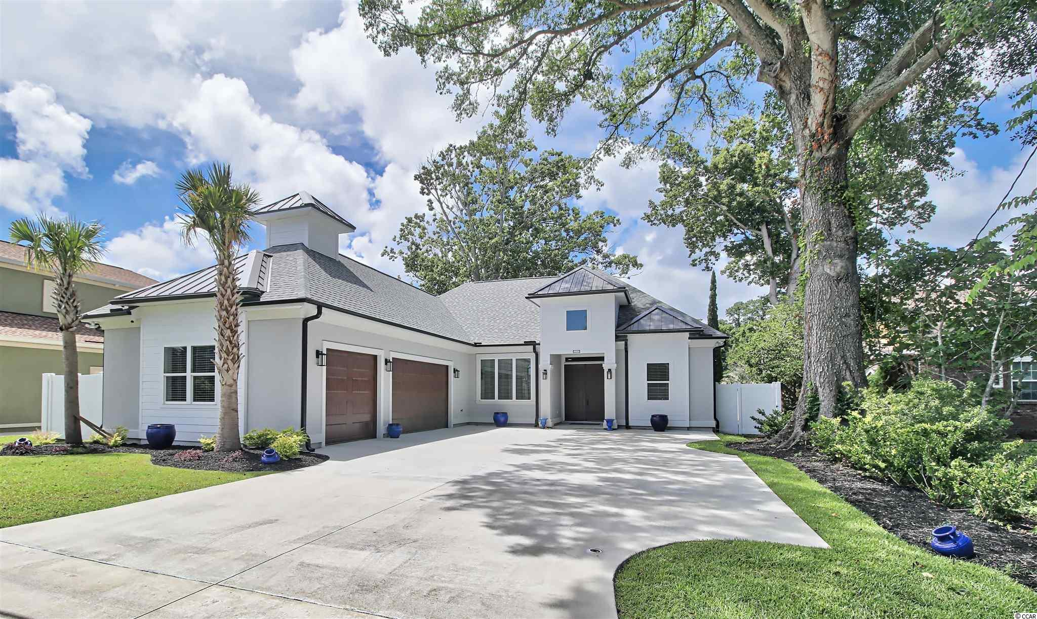 """Welcome to Myrtle Beach's best kept secret: WATERSIDE DR, a centralized, intracoastal waterway, no HOA, no flood zone neighborhood with a private boat ramp! This custom WATERFRONT home was finished in August of 2020. It sits on a rare 70' x 200' lot on a dead end street. At the front of the house is a 300+ year old oak tree. At the rear is a 200+ year old white oak, both of which are gorgeous and provide incredible shade to the property. This one-of-a-kind contemporary warm bright and airy home offers a three car garage, a driveway that can accommodate up to eleven vehicles, an open and split floor plan with 10' ceilings, a 12' tray with stained beams in the main living area, and 11' trays in the master, dining, and den/office - all of which have dimmable LED ambient lighting. 8"""" x 48"""" wood-look porcelain tiles cover the floors throughout minus the bathrooms. Those have something even more special (see photos). The kitchen features soft close cabinetry, quartz countertops, subway glass tile backsplash, dimmable under cabinet lighting, and top of the line KitchenAid stainless appliances, including a hood over the range and a built in wine cooler and dedicated ice maker. A farm sink tops the large 114""""' x 44"""" island. Quartz countertops are also found in both baths, laundry, and cabinets next to the 8' wide, floor-to-ceiling stone electric fireplace. The master suite's spa-inspired bath has a large soaking tub inside the huge four-head shower, including a 16"""" rainfall. The master's oversize walk in custom closet is spacious and also features soft close drawers. Wainscoting surrounds the dining area. The backyard is enclosed with a combination of a 6' vinyl and a 4' metal fence. The home is hardwired with interior and exterior sound and surveillance. LeafFilter gutter protection system in place. The lanai is ready for an outdoor kitchen with water and power already in place. An elaborate covered boat lift and floating dock permit in hand too! Across the waterway is a 27"""