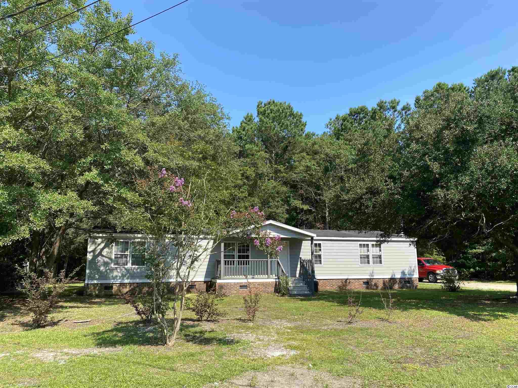 """Permanently affixed 3 bedroom, 2 bath manufactured home with approx. .37 acres. Spacious open floor plan with oversized rooms. Several upgrades within last 2-3 years include hardiplank siding, refurbished bathroom showers, shiplap, laminate flooring, etc. Enjoy the outside on the side porch or large deck overlooking the back yard. A little TLC and this will be a true gem. This home is at the end of a cul-de-sac providing privacy and is conveniently located near schools, shops, Pawleys Island beach, and the Waccamaw River.  Cash offers only - being sold """"As Is"""". Seller will not do any repairs."""