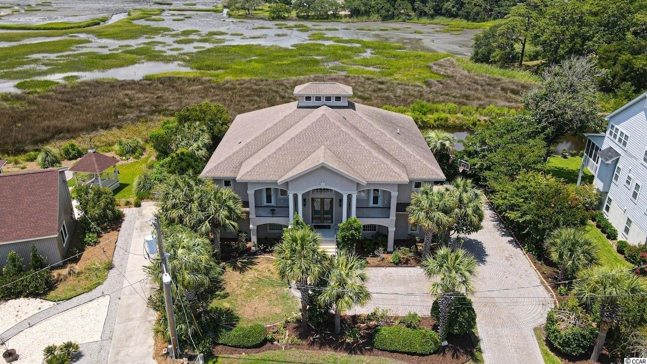 This STUNNING 4 bedroom, 4 full bathroom family home located ON THE MARSH and ONLY 2 MINUTES TO THE BEACH with NO HOA features a spacious, bright, and open floor plan! The vaulted living room features large sliding glass doors giving gorgeous views and lots of natural light, custom shelving that pull out to reveal hidden bookshelves, a warm fireplace, and a custom painted skylight! The gourmet kitchen features lovely wood cabinetry, custom tile backsplash, granite counter tops, an island with a built-in wine rack, a breakfast bar, a wine cooler, and a walk-in pantry plus a dining area! The elegant master suite boasts private access to the balcony, separate his and her walk-in closets, and an impressive master bathroom complete with heated tile floors! This amazing home also features a huge bonus/recreation room and a spacious office! You will enjoy the spectacular weather and breathtaking Marsh views from the spacious screened balcony or the patio perfect for entertaining and grilling out complete with a dedicated bull propane line! There's also an outdoor shower and a tankless water heater! Being in such a great location, not only are you a short golf cart ride to the beach, but you are also only minutes to Barefoot Landing, Tanger Outlets, delicious restaurants, shops, and so much more! Don't miss out out his incredible opportunity and book your showing today!