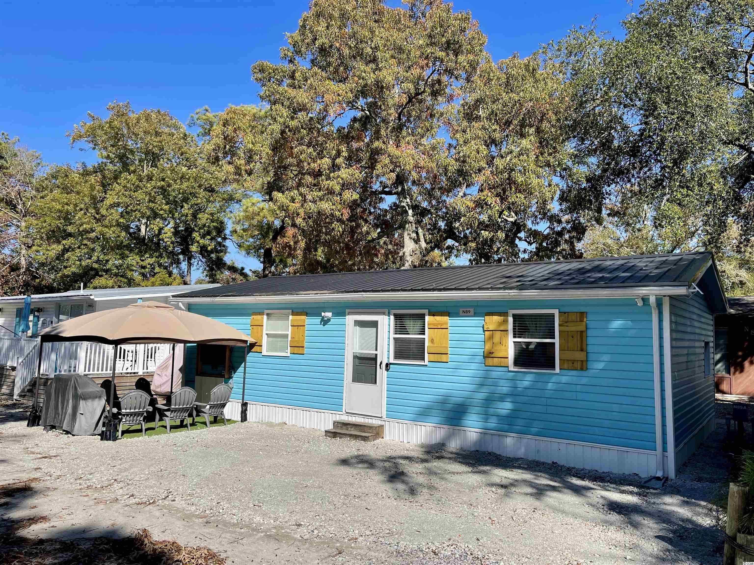 TURNKEY INVESTMENT ON THIS NEWLY UPDATED 2 BED/2 BATH BEACH HOUSE w/ BUNK HOUSE, NEW EVP FLOORING, NEW KITCHEN, NEW MASTER BATH AND A NEW METAL ROOF. Located in the central part of the park and close to all amenities, this home has a wonderful open floor plan and tons of NEW UPDATES including, new kitchen countertops, cabinets, sink, stainless steel appliances, new master bath walk-in shower, vanity/sink, pedestal sink, toilets, new shiplapped walls, new paint, new fixtures, new flat screen TVs, new outdoor shower with hot/cold water, new outdoor TV and viewing area and more! Property comes fully furnished and includes all appliances, washer/dryer, furnishings and decor. Home is on a rental program and is only available to show during the Summer between 1-3 on Sundays. Must honor 2021 rentals.   There is no HOA in Ocean Lakes however, all home sites are located on leased land, which are payed in semiannual installments due in January and July.   Amenities abound in Ocean Lakes' gated community and include one mile of pristine white sand beach, 24 hour security, trash pick-up, indoor/outdoor swimming pools, water park/slides, lazy river, splash zone, 2 full size basketball courts, miniature golf, fire pit, corn hole, shuffle board, horseshoes, ping-pong, Sandy's Down-under skatepark, recreation building, arcade, general store, golf cart rentals, Sandys Meet & Eat restaurant and more!