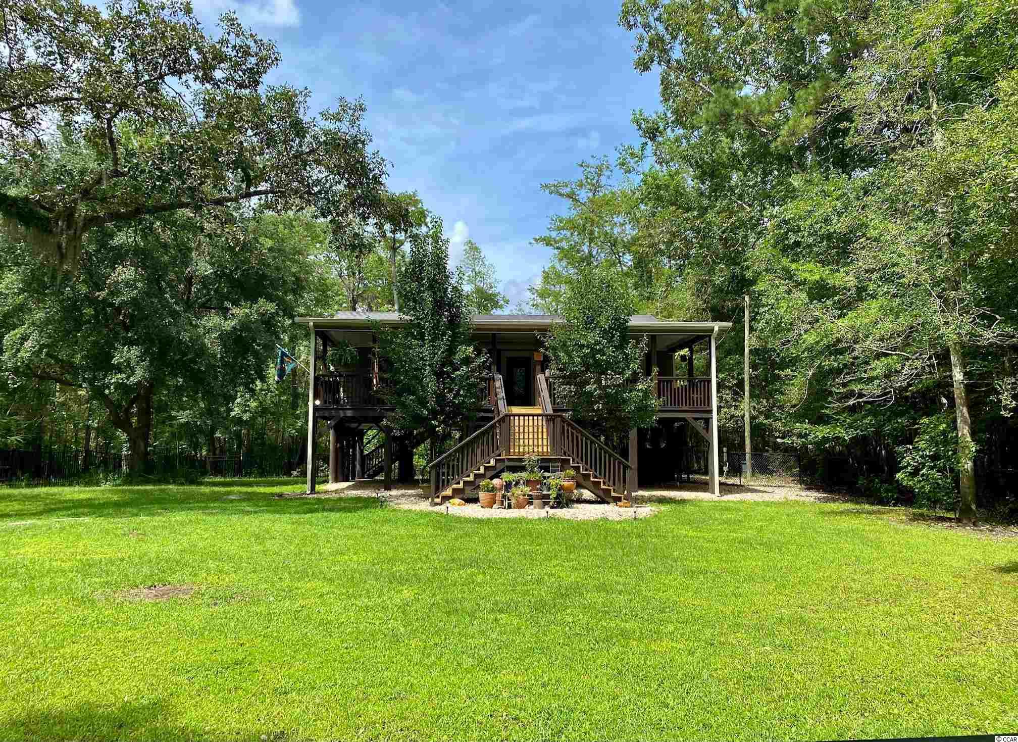 This home, as well as the property it is on, is an absolutely beautiful private Oasis! This 3BR/3BA single family home is positioned near the back of the property, allowing for a large front yard with large fenced portion. There is a semi private pond in the back yard to accommodate a small floating dock and is great for fishing or just trolling in a boat relaxing and enjoying the sounds of nature. This is a spacious three bedroom home with plenty of room for entertaining. Outdoor living areas include a 530 sq. ft. front porch perfect for your morning cup of coffee or afternoon cocktail, listen to the birds song and look out to see wild turkey and an occasional deer running through. The screened in back porch has cable TV hook-up and a back deck overlooking the pond. Fantastic solid fenced portion below home is perfect for storing your toys! Less than a mile to the local boat landing.  Come make this piece of paradise your very own! Owner is a licensed South Carolina Realtor.