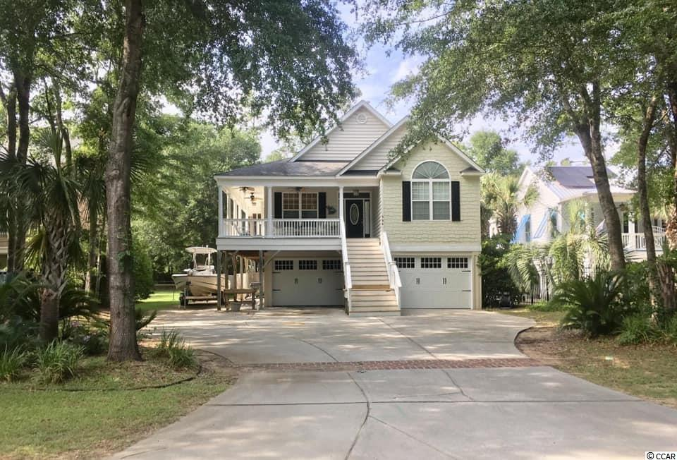 Beautiful home in the heart of Murrells Inlet.  3 BR/ 2 Bath upstairs main home with almost 1500 HSF.  Another 400 sf of heated & cooled EZ breeze sunroom with a wood burning fireplace.  Granite and stainless steel appliances in kitchen.  Granite in Master Bathroom and Tile walk in shower with glass enclosure.  Hardwood and tile throughout with the exception of the master bedroom which is currently carpeted but has same hardwood underneath.  Large Back deck, huge fenced in back yard, with an additional/detached garage with tall ceilings and a storage room above.  1BR/1BA apartment with separate entrance that includes living room, full kitchen and washer/dryer.  Ground level back patio is covered with a wood burning fireplace and outdoor shower.  Minutes to Marsh Walk and Public Boat Landing.  No HOA.