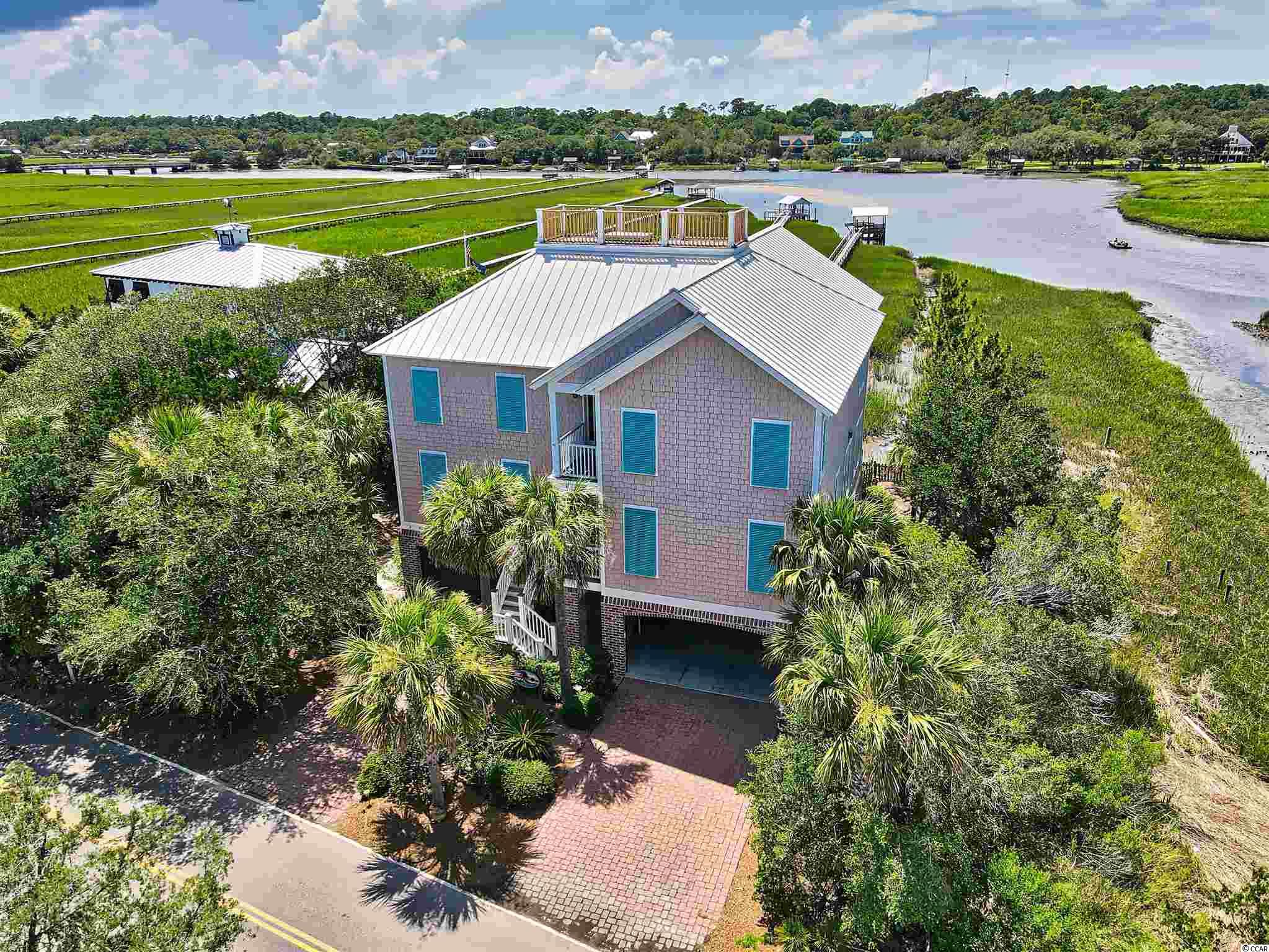 """One in a lifetime opportunity to own the perfect beach house.  Nestled along Pawleys Island's scenic creek and mere steps from the sand of the historic beach, this 5 BR/5 1/2 bath home is loaded with unique features.  From the incredible views to the expansive dock, elevator and """"widow's walk"""" perched high atop the home, this is the perfect place for memories to be made."""