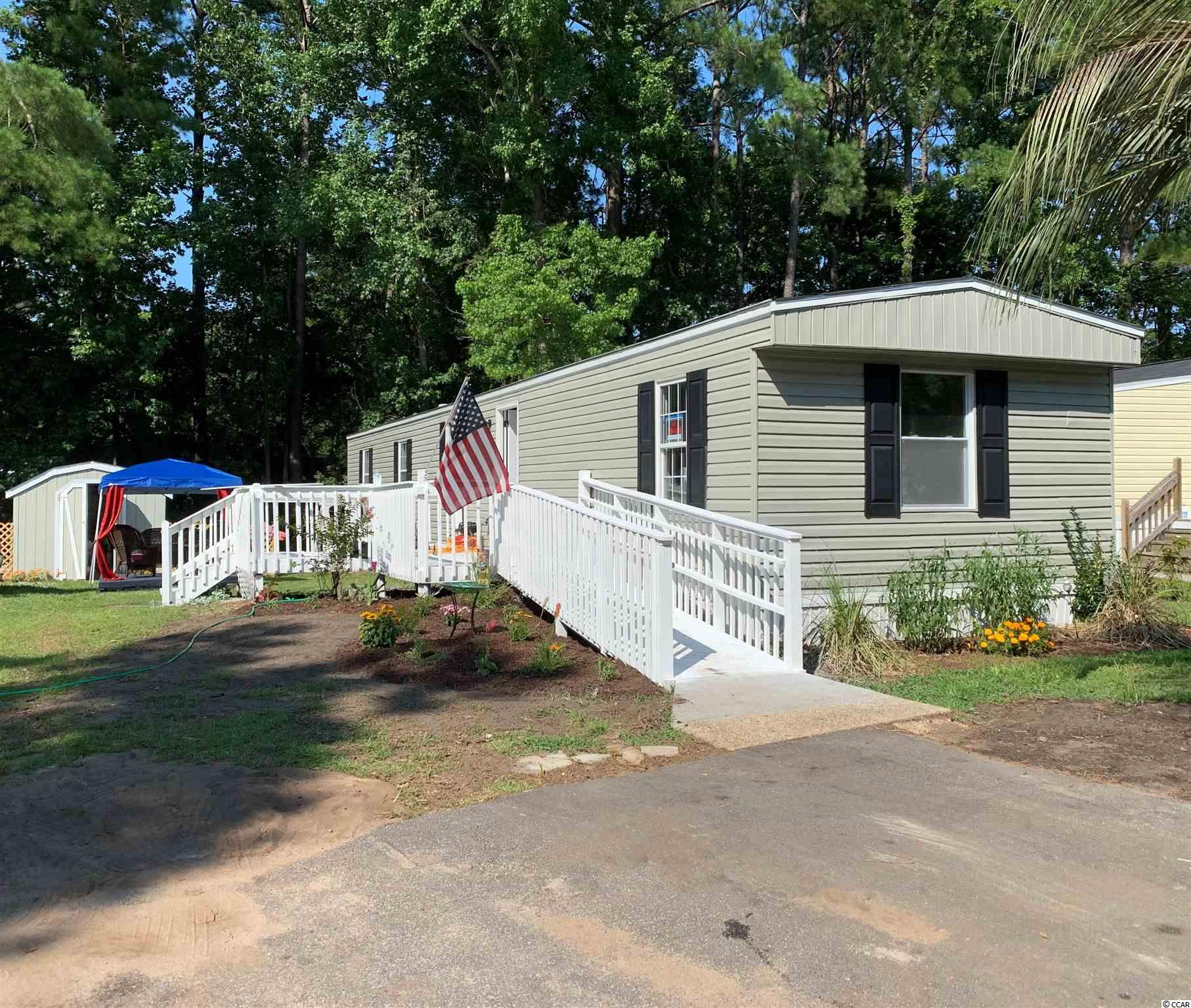 Fully Renovated & Great Location!!! Move-in-Ready Manufactured Home Less than a Mile from the Beach!!! This mobile home sits in the very popular and golf-cart friendly Windjammer Village section of Murrells Inlet/Garden City. Brand new luxury vinyl flooring, stunning shiplap ceilings and new drywall throughout, both bathrooms renovated, new shower/tub surrounds and toilets. Stainless Steel kitchen appliances. Windows, washer/dryer, siding and doors replaced. Ramp, porch area painted and new plantings. Two HVAC digital split-units barely used (2019) & work great! New Kitchen and bathroom layouts. Tons of storage inside and out in the large shed which conveys with sale. Golf cart and boats are both acceptable in this community. Neutral paint and wainscoting complete this transformation. Shopping, great restaurants and medical all nearby. Be at the heart of everything in your own perfect beach bungalow. All measurements are approximate and must be verified by buyer prior to closing. Book your showing today!!!
