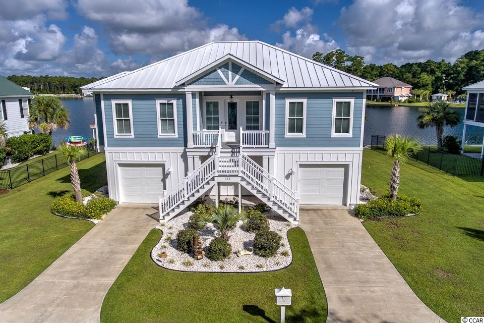 """Custom-Built Lake House at The Beach - True Southern Lifestyle! Fresh Water Spring Fed Lake in your backyard and the Atlantic Ocean, Intracoastal Waterway and famous Marsh Walk less than 10 minutes away. What more could you ask for! This Port City Homes custom built raised """"beach house"""" truly has it all featuring 4 bedrooms, 3.5 bathrooms with an open floor concept overlooking the large 22-Acre Stocked Lake. A beautifully appointed elevator brings you from the garage to the main/upper level of the home where you will find the Owner's Suite, walk-in closet and bathroom with a large tiled shower, Toto Toilets and heated floors, half bathroom and a guest bedroom with its own private bathroom. On the lower level, you will find 2 guest bedrooms with a shared bathroom. MANY UPGRADES were made to this gorgeous, immaculate home - the attention to detail surpasses them all such Tankless Hot Water Heater, Kitchen Aid Stainless Appliances, 10-ft ceilings on the main level, 3-zone HVAC unit with WIFI thermostats, surround sound system, security system, added insulation in the interior walls for sound reduction, upgraded baseboards and crown moldings with beadboard ceilings in the Owner's Suite and Screen porch, oversized garage with 8 ft tall garage doors and one stall is 25 ft long sure to fit most modest sized boats, Seawall, Custom pavers/firepit, Docks with Electric Outlets, 4-zone irrigation system with lake pump, Outdoor Shower and so MUCH MORE. From matching hardwood flooring and wainscotting in the elevator to the 325-gallon buried propane tank ready to support that heated pool you always wanted, do not let this RARE OPPORTUNITY to own a Custom-Built Lake House at the Beach. Wind down your day enjoying the summer night breezes as you watch the sun set from the comfort of your screen porch. This quaint, gated community is located in the Heart of Murrells Inlet and is adjacent to Brookgreen Gardens.  Nearby are many restaurants, a hospital, grocery stores, boutique shoppi"""