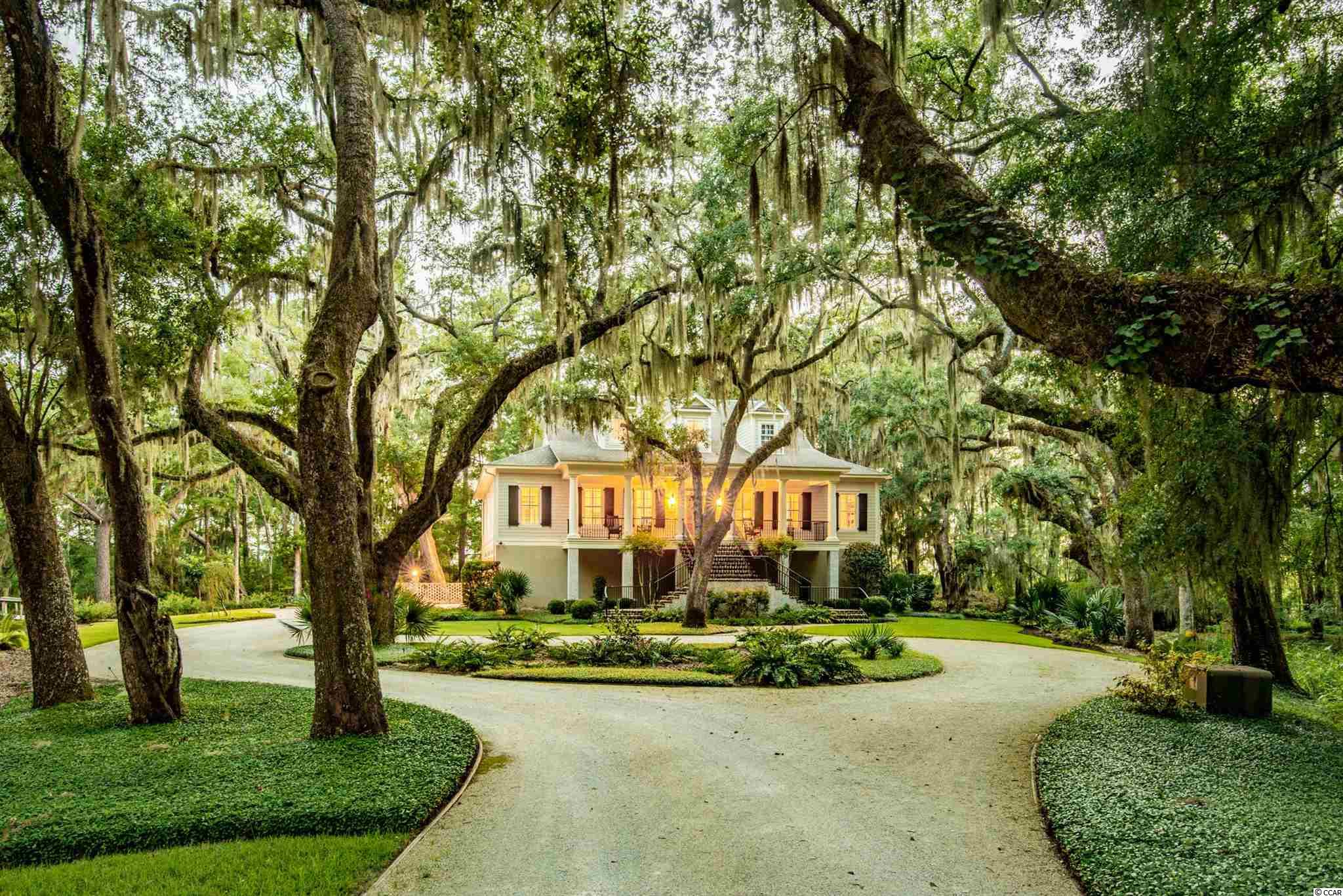 """Welcome to 'The Landing"""" in the Oak Pointe Estates section of Willbrook Plantation. This premier custom-built home sits on 1.75 acres that once housed the plantation barns and warehouses along Oatland Creek. Owners have access to the Intracoastal/Waccamaw River from the private dock. Nestled under moss-covered live oaks that have beautiful up-lighting at night and lush landscaping, this home has it all. Features include Hardi plank and brick exterior, upgraded Andersen windows, elevator to all levels, a gas burning fireplace, Rinnai tankless water heater with a 59-gallon holding tank, 6-inch galvanized gutters, fenced in back yard with a bulkhead, Circa lighting, interior handmade stair rails, Brazilian wood floors, plantation shutters, surround sound throughout, and security system. There is a well for the irrigation system that also works pulling water from the river.  The main living area is open with a chef's kitchen that includes a Wolfe range with antique fireback, custom-built soft close cabinets, and Italian countertops. Walk-in Pantry features a built-in desk, wine cooler, and laundry area with plenty of storage.  Living area with custom cabinets and gas burning fireplace opens up to the magnificent porch that runs the length of the home with amazing views! Two seating areas along with a dining table make this a perfect spot to enjoy the views, sunsets, and wildlife this location has to offer. The porches have outdoor speakers, 4 water faucets, and TVs. There is also an inviting front porch with rocking chairs. The powder room and wet bar lead into the office. There are spectacular views from every window!  The Owners Suite is on the main level complete with custom-built shelves in the closet, a beautiful bathroom with a walk-in shower, tub, and Italian counters. Nice sitting area with doors leading to the porch. Custom window treatments. Upstairs features three ensuite bedrooms with custom tiled bathrooms (two showers and one tub and pedestal sinks). All r"""