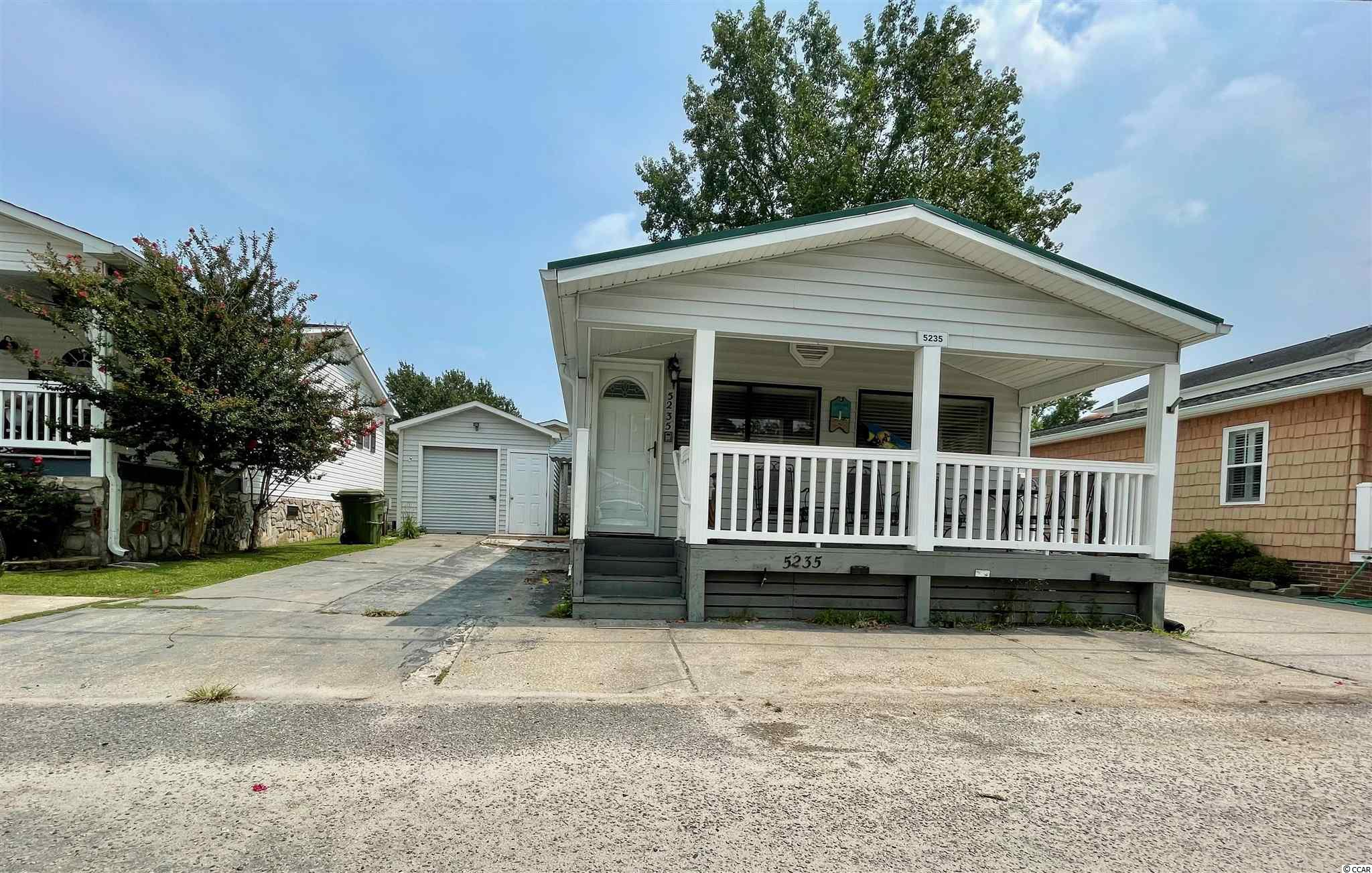 NICE 3 BEDROOM/2 BATH BEACH HOUSE W/ AN OPEN CONCEPT FLOOR PLAN, COVERED PORCH AND A DETACHED GARAGE LOCATED ON N. SANDLAPPER DRIVE IN OCEAN LAKES. Located in the highly desired 5,000 section, close to Sandlapper Lake and all amenities. Home comes fully furnished including golf cart! New metal roof in 2018. Home is on a rental program. Must honor 2021 rentals. Measurements are not guaranteed and should be verified by buyer's agent.   There is no HOA in Ocean Lakes however, all home sites are located on leased land, which are payed in semiannual installments due in January and July.   Amenities abound in Ocean Lakes' gated community and include one mile of pristine white sand beach, 24 hour security, trash pick-up, indoor/outdoor swimming pools, water park/slides, lazy river, splash zone, 2 full size basketball courts, miniature golf, fire pit, corn hole, shuffle board, horseshoes, ping-pong, Sandy's Down-under skatepark, recreation building, arcade, general store, golf cart rentals, Sandys Meet & Eat restaurant and more!