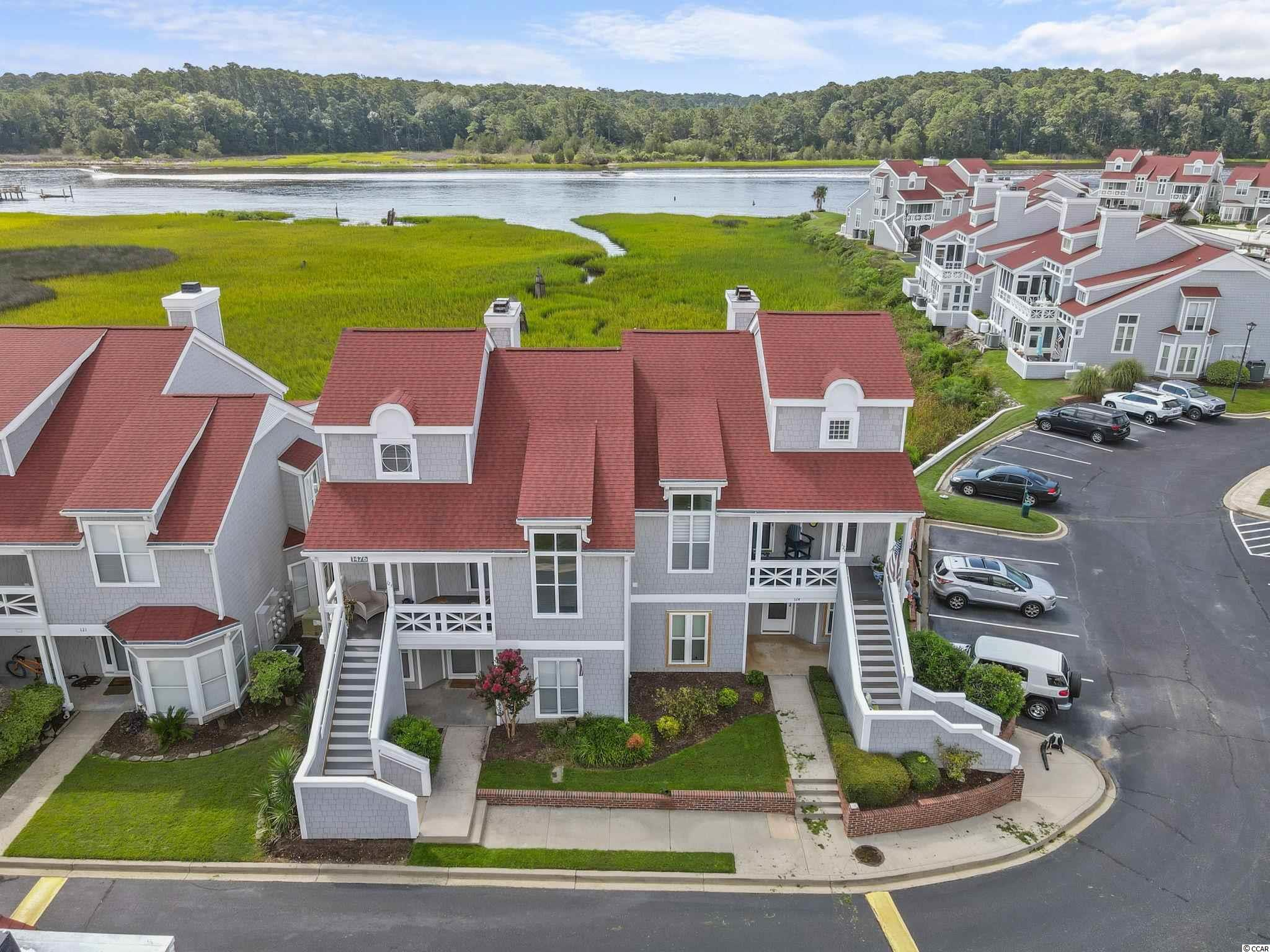 """DIRECT Intracoastal WATERWAY VIEWS from this rare listing in Mariners Pointe in Little River, SC.    # 123 Mariners Pointe has one of the BEST VIEWS in this gated waterfront and marina community.   This condo has 2 full bedrooms and 2 full bathrooms PLUS a loft on the 2nd floor that makes a great home office, play room, or small bunk bedroom.   This 2-story condo has a nice foyer entry with a coat closet to your left once you enter.  The stairs to the 2nd floor are in front of you.   The spacious kitchen features a pass-through window to the dining area.   The kitchen also has: Tiled countertops and backsplash; white porcelain sink; smooth-top range; built-in microwave; crown molding; a breakfast nook; all kitchen appliances (refrigerator, stove/oven, microwave, and dishwasher; and a large washer/dryer closet fit for a side-by-side washer/dryer).   The dining area is in between the kitchen and the living room and has crown molding.   The sunken living room features a cathedral ceiling, built-in shelving, and an electric fireplace.  There is 1 bedroom on the 1st floor with his-and-her closets, and it's connected to a full bathroom with tiled sink-top, crown molding, an oval mirror with decorative lighting, and a tub/shower combo.  Upstairs is the loft, along with the owner's suite.  The owner's suite has direct views of the Waterway, crown molding, a ceiling fan, and walk-in closet.  The owner's suite bathroom has 12"""" diagonally-laid decorative tile, 6"""" tiled sink-top, framed mirror, decorative lighting, crown molding, and a huge tiled corner shower.   #123 Mariners Pointe has a covered front porch, an outside storage closet, and a spacious rear balcony with peaceful views of the marsh and Intracoastal Waterway.  All of the decking on both the front porch and rear balcony is all-new Trex decking just installed in June 2021.   The front steps leading to the condo were also replaced in May 2021.  New 5"""" LVP flooring was installed in the entire downstairs in 2020.  Also"""